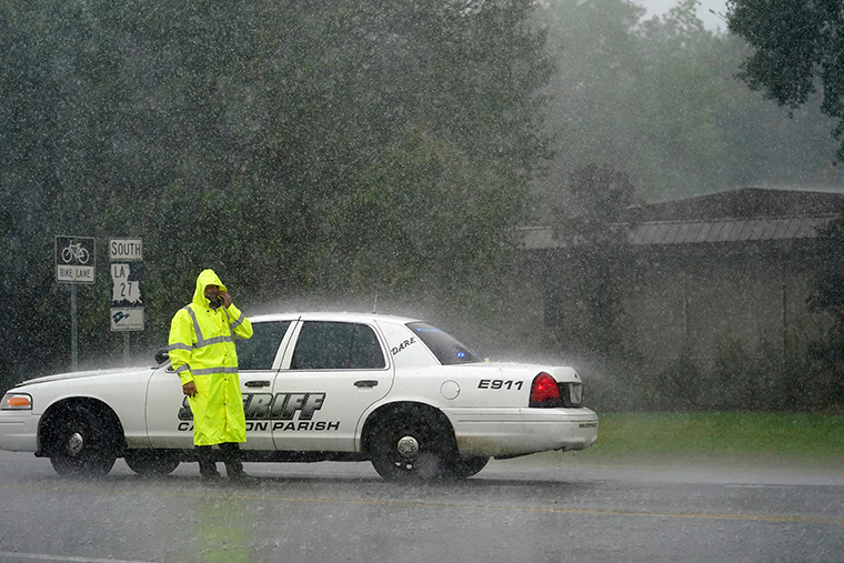 A Cameron Parish Sheriff deputy wipes his face as he mans a roadblock in the rain on LA 27 while residents evacuate Cameron in Lake Charles, Louisiana, Wednesday, August 26, ahead of Hurricane Laura.