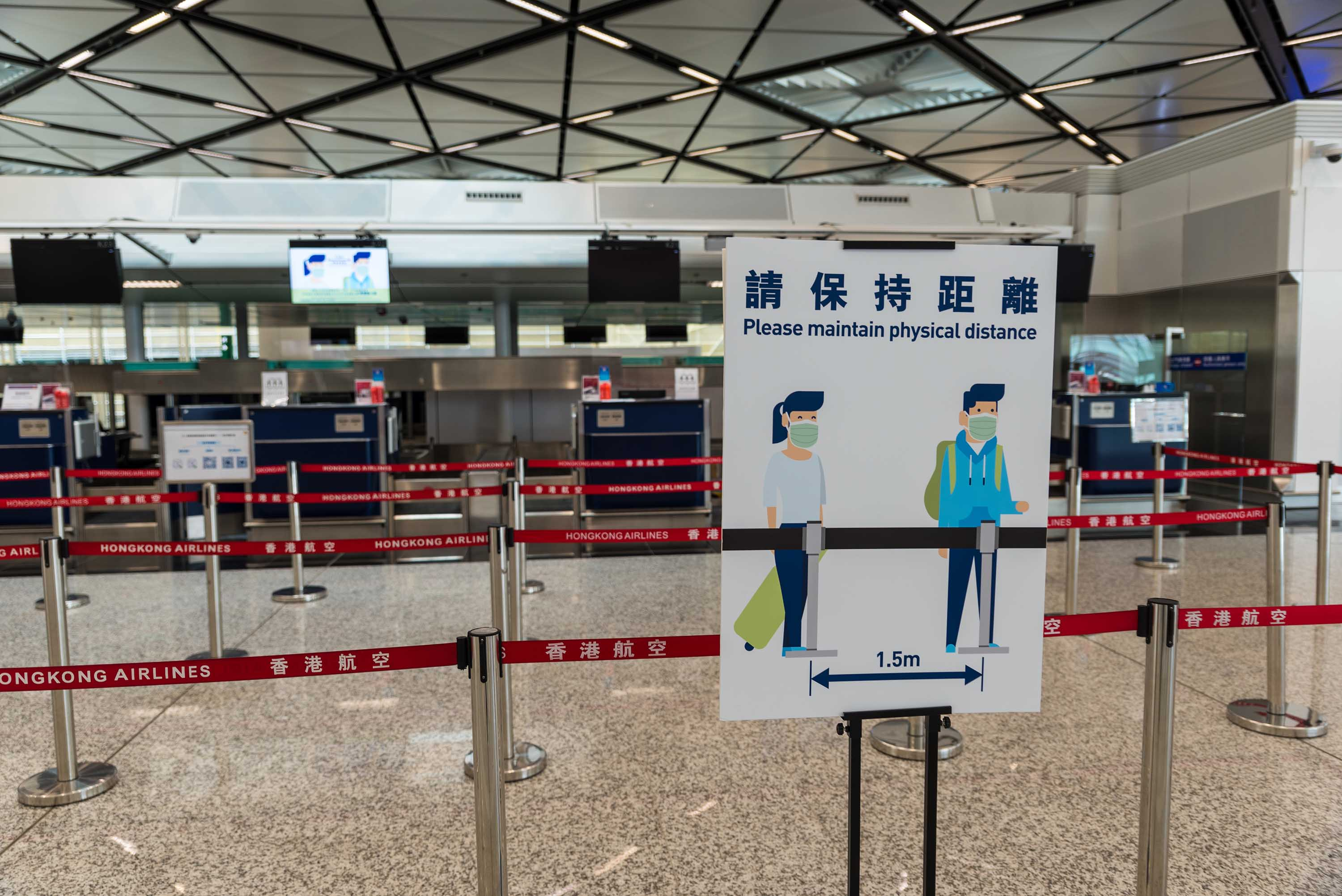 Social distancing guidance is posted on a sign in the check-in area at Hong Kong International Airport on September 4.