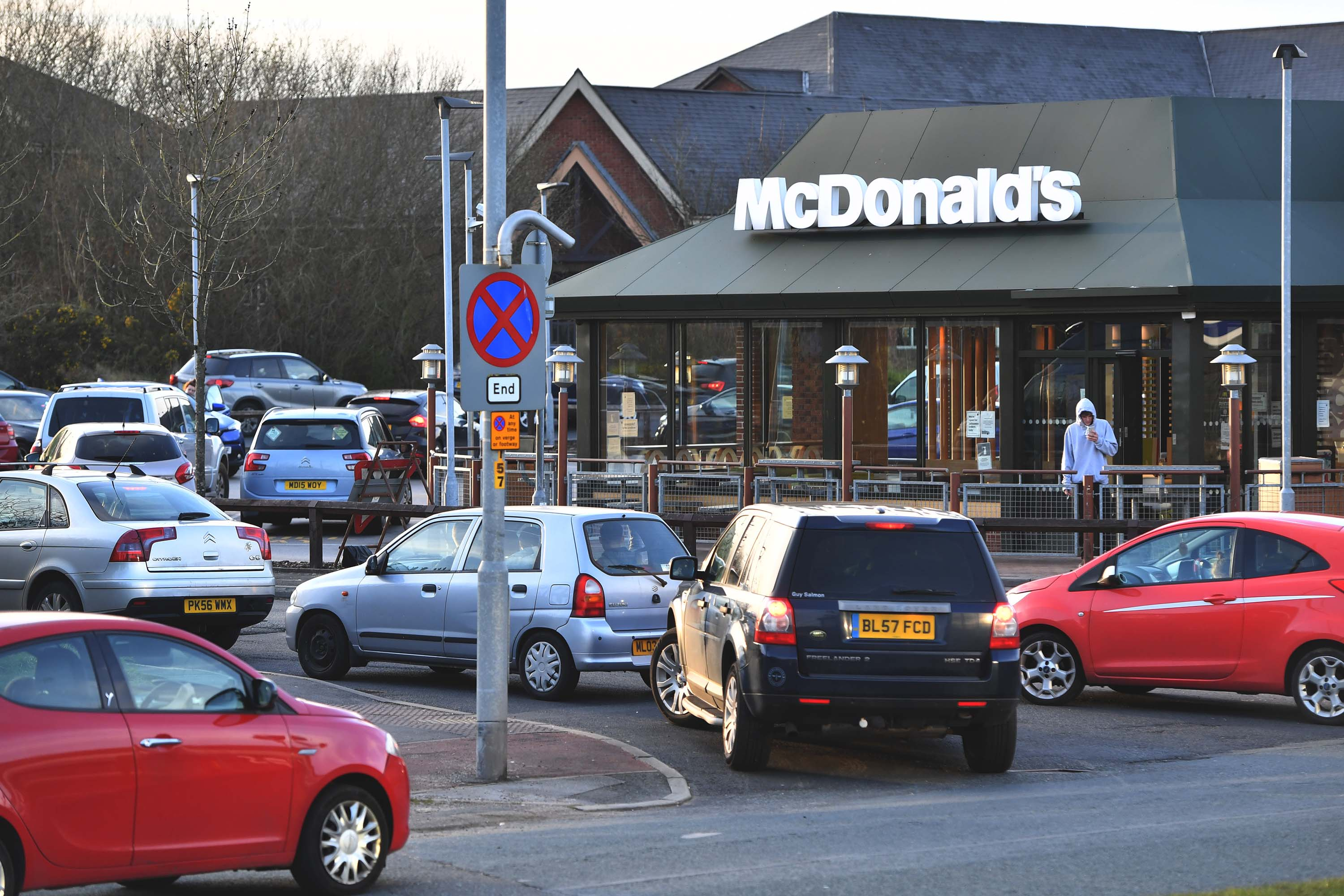 People queue outside a McDonalds restaurant in Hattersley, England, on March 23, after the chain announced it would close its restaurants.