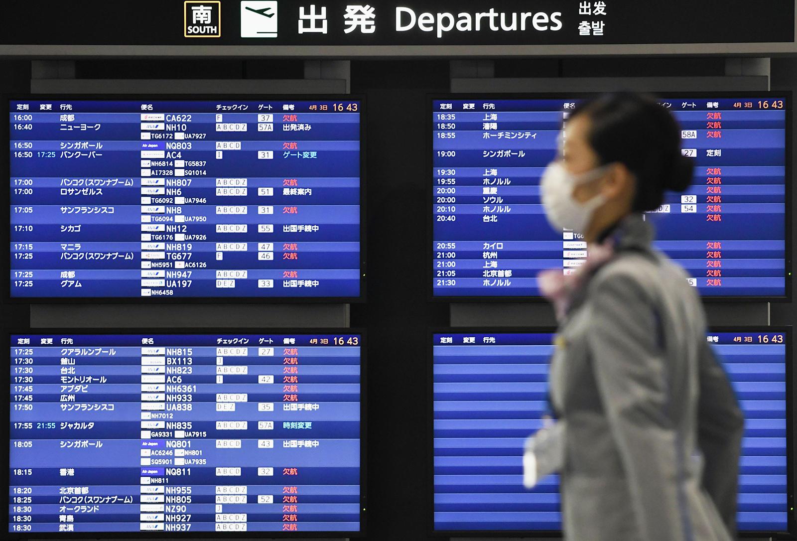 A woman walks past the departure board at Narita airport near Tokyo, on April 3.