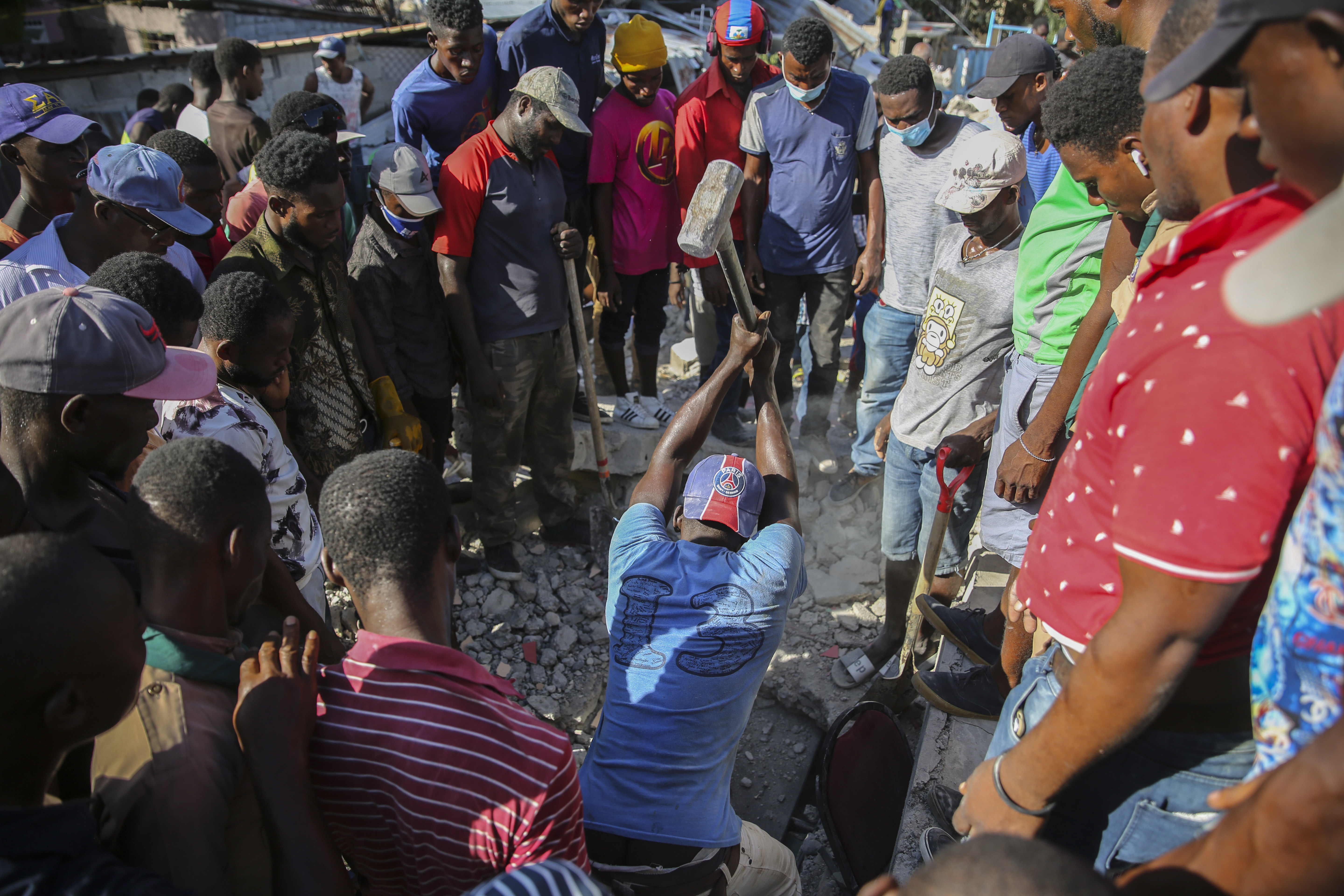 A man uses a sledgehammer in an attempt to rescue people from the rubble of a home destroyed following a 7.2 earthquake, in Les Cayes, Haiti, on August 14.