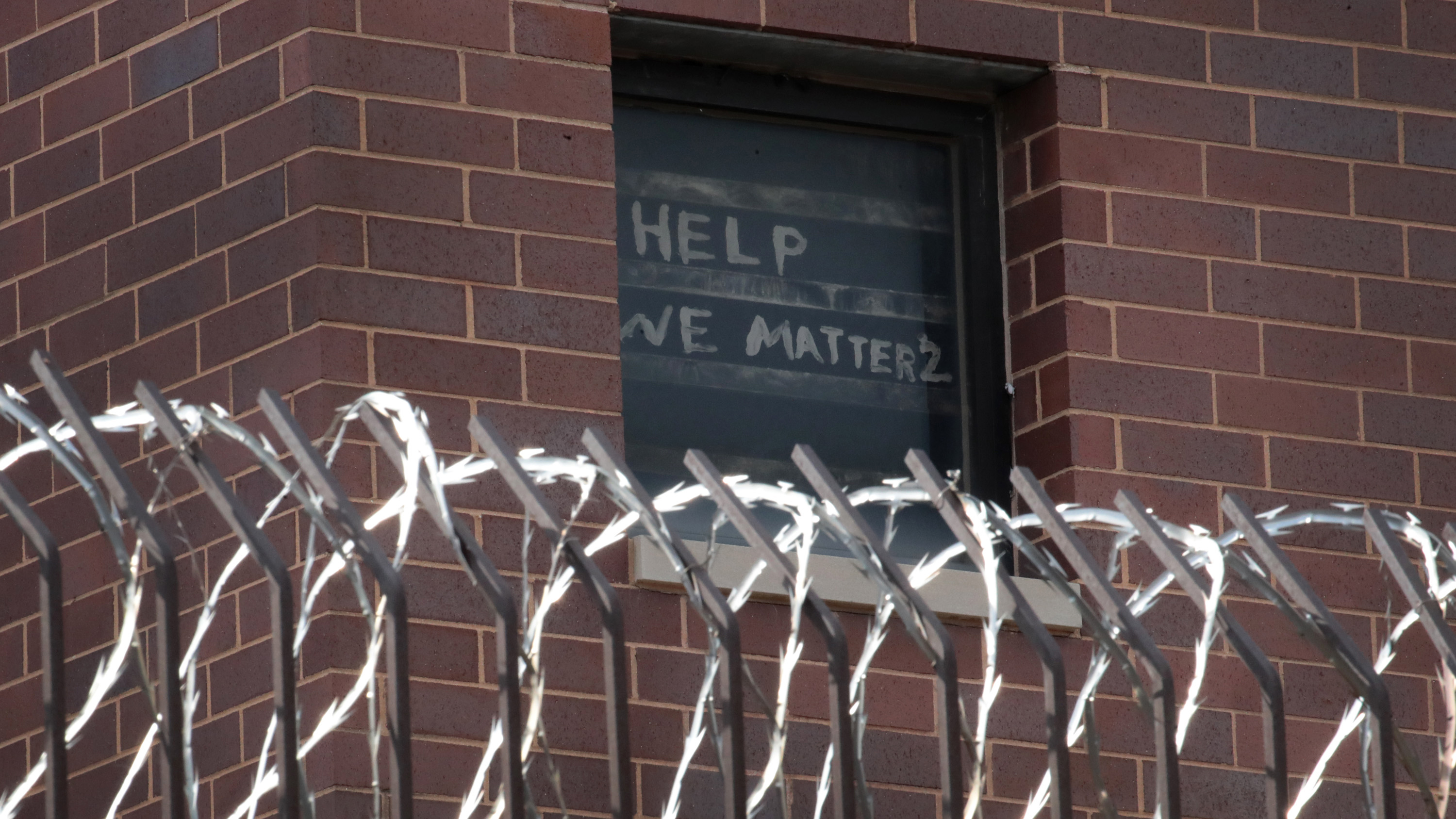 A sign pleading for help hangs in a window at the Cook County Jail in Chicago, Illinois, on April 9.
