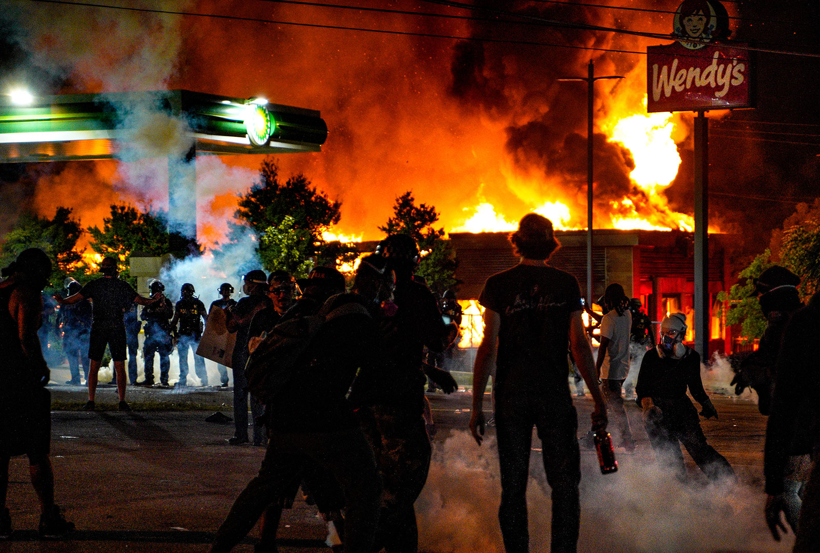 Demonstrators watch a Wendy's restaurant burn in Atlanta during a protest over the shooting of Rayshard Brooks.