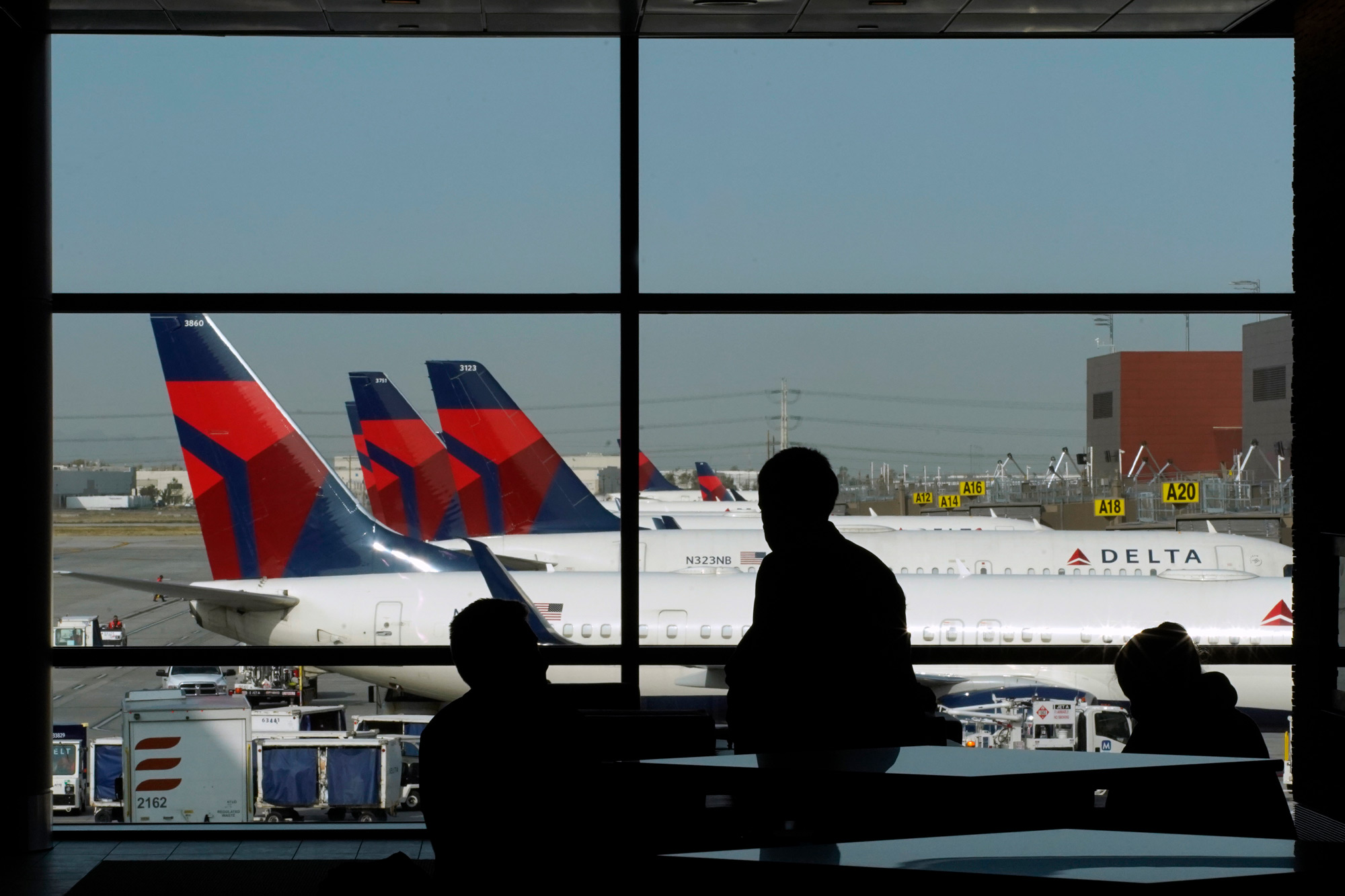 Travelers wait for flights as Delta Air Lines planes sit at gates at the Salt Lake City International Airport in Salt Lake City, Utah, on September 15.