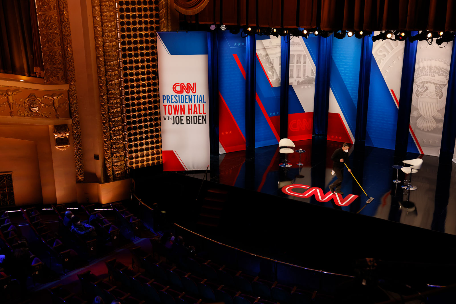 A crew member wipes down the floor before CNN's town hall with President Joe Biden at the Pabst Theater.