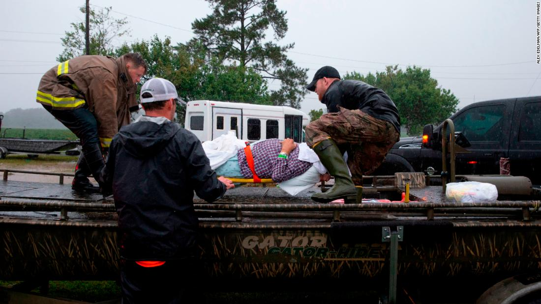 Members of the Cajun Navy and emergency workers place a nursing home patient on a boat during the evacuation of a nursing home due to rising flood waters in Lumberton, North Carolina, on September 15, 2018 in the wake of Hurricane Florence.