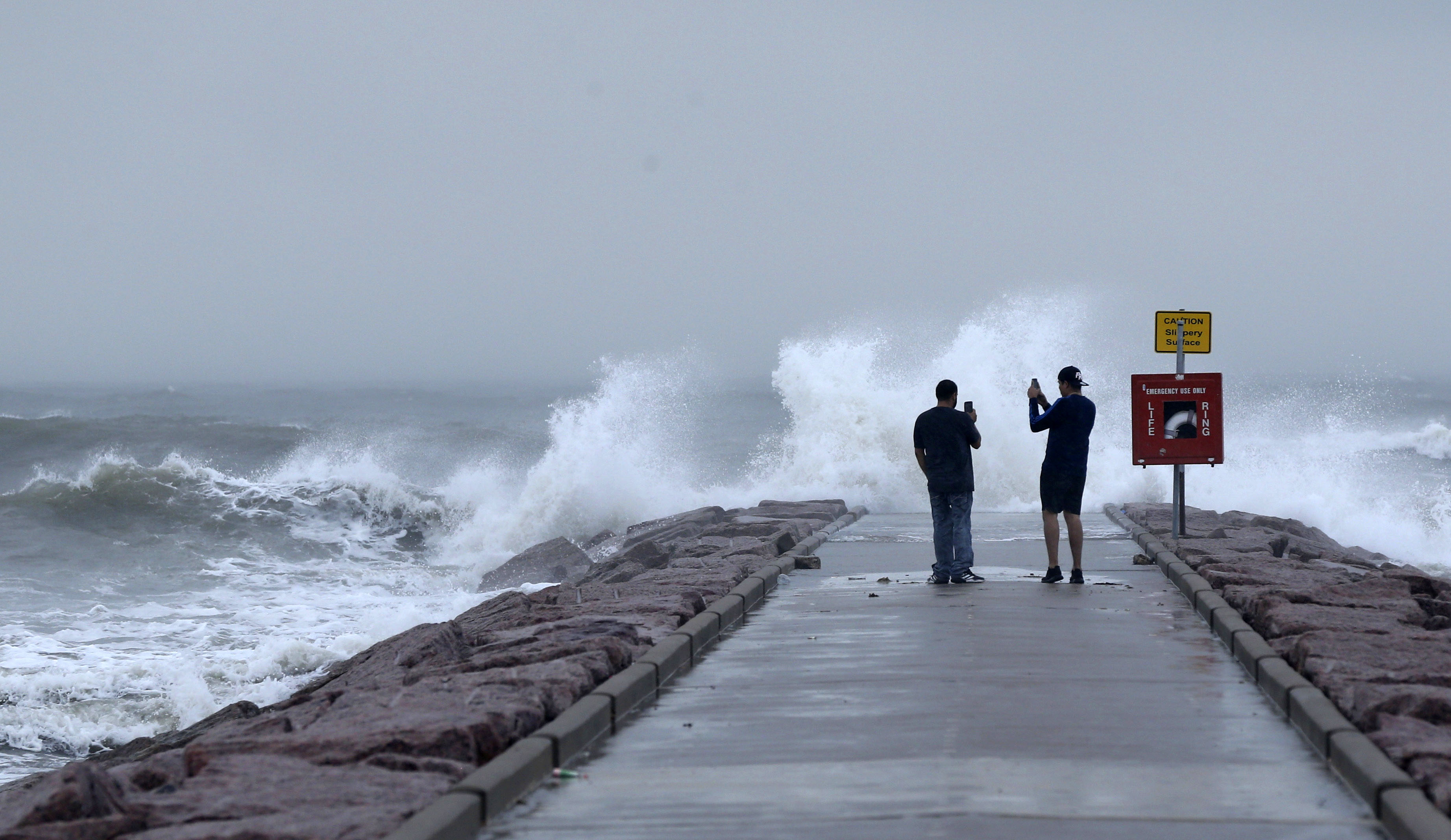 People photograph waves in Galveston, Texas, on August 26.