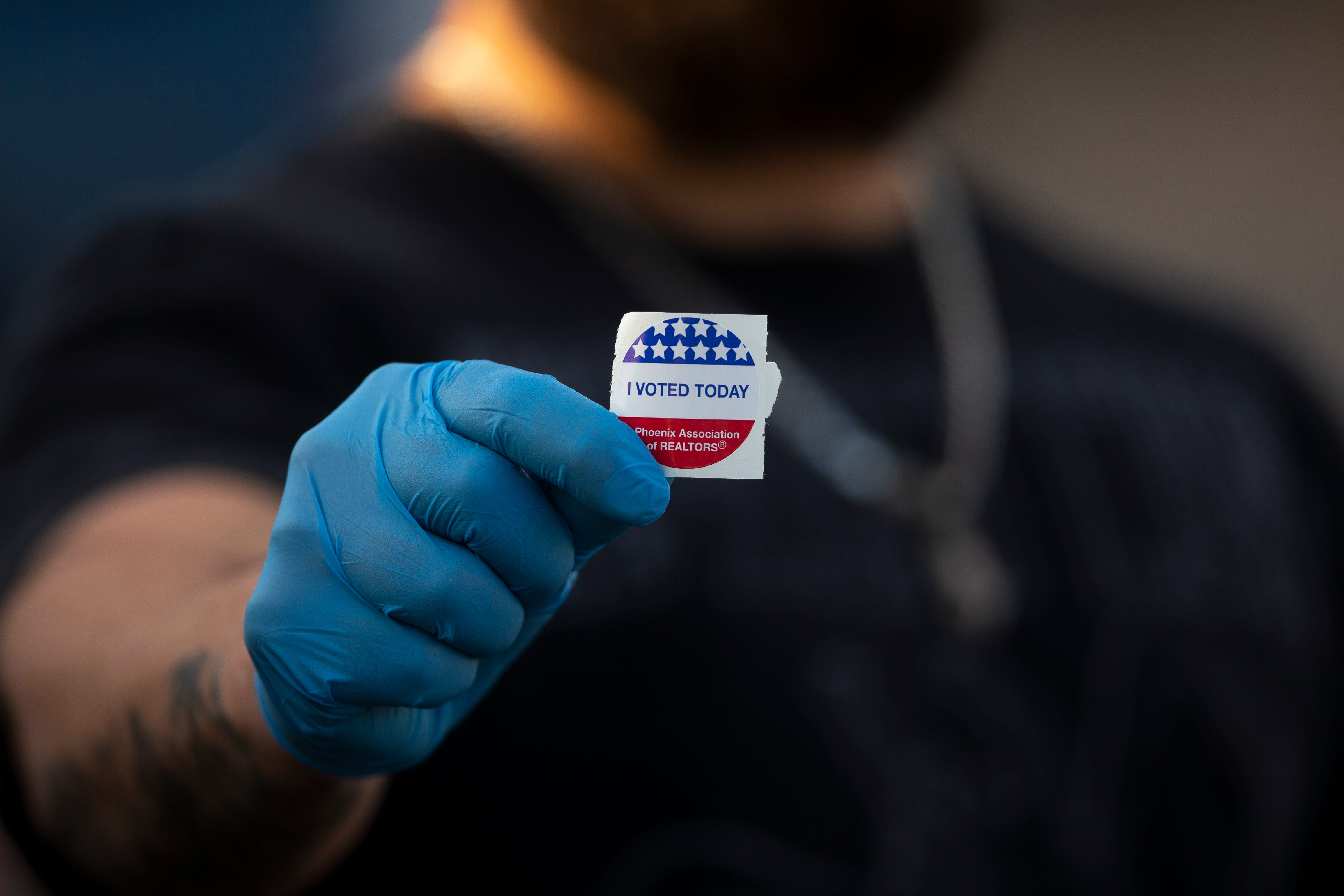 An Arizona voter holds a sticker showing he voted in the Democratic Primary election at the Burton Barr Central Library in Phoenix on March 17.