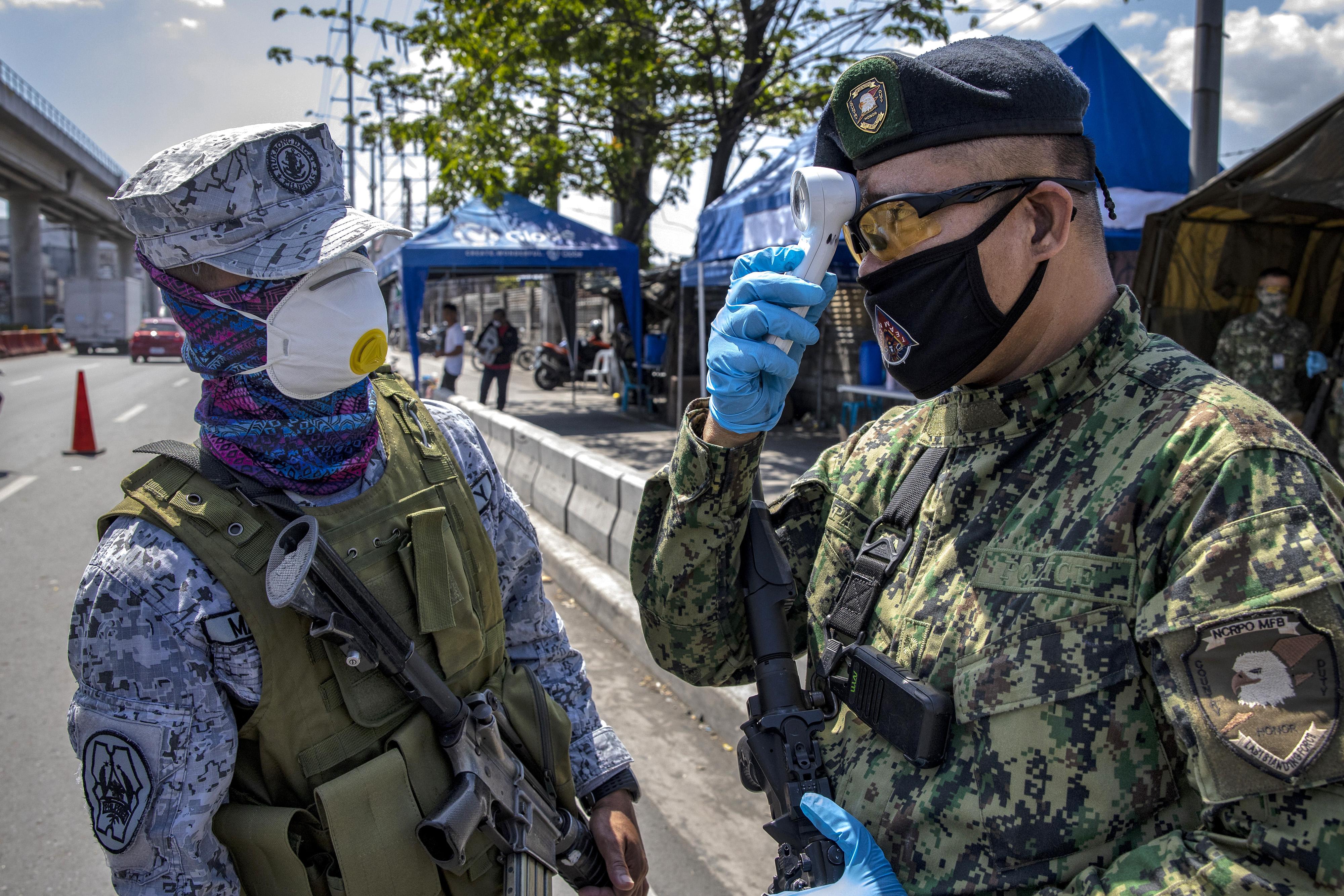 A Filipino policeman checks his own temperature at a quarantine checkpoint on Wednesday in Marikina, Metro Manila.