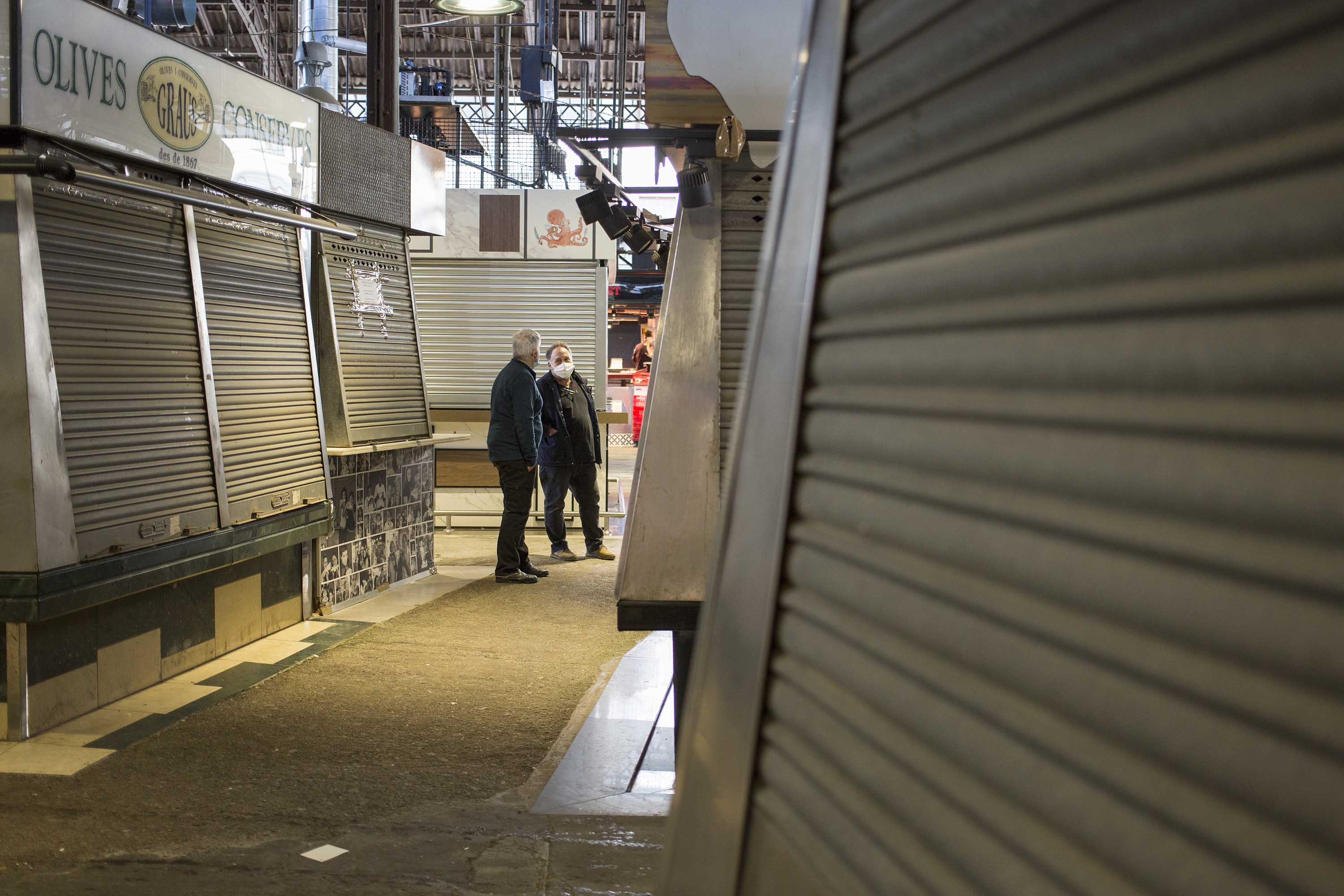 Workers are seen amid closed stalls at a market in Barcelona, Spain, on April 23.