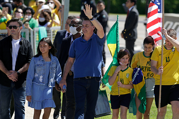 Brazil's President Jair Bolsonaro holds his daughter's hand as he waves to supporters during a protest against his former Minister of Justice Sergio Moro and the Supreme Court, in front of the Planalto presidential palace, in Brasilia, Brazil, Sunday, May 3.