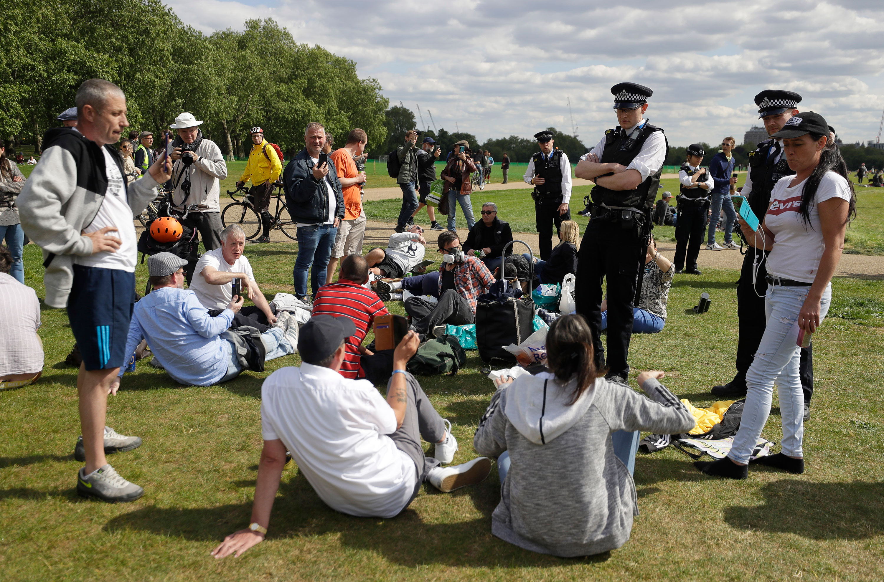 Police speak to people during a mass gathering protest in Hyde Park in London on May 16.