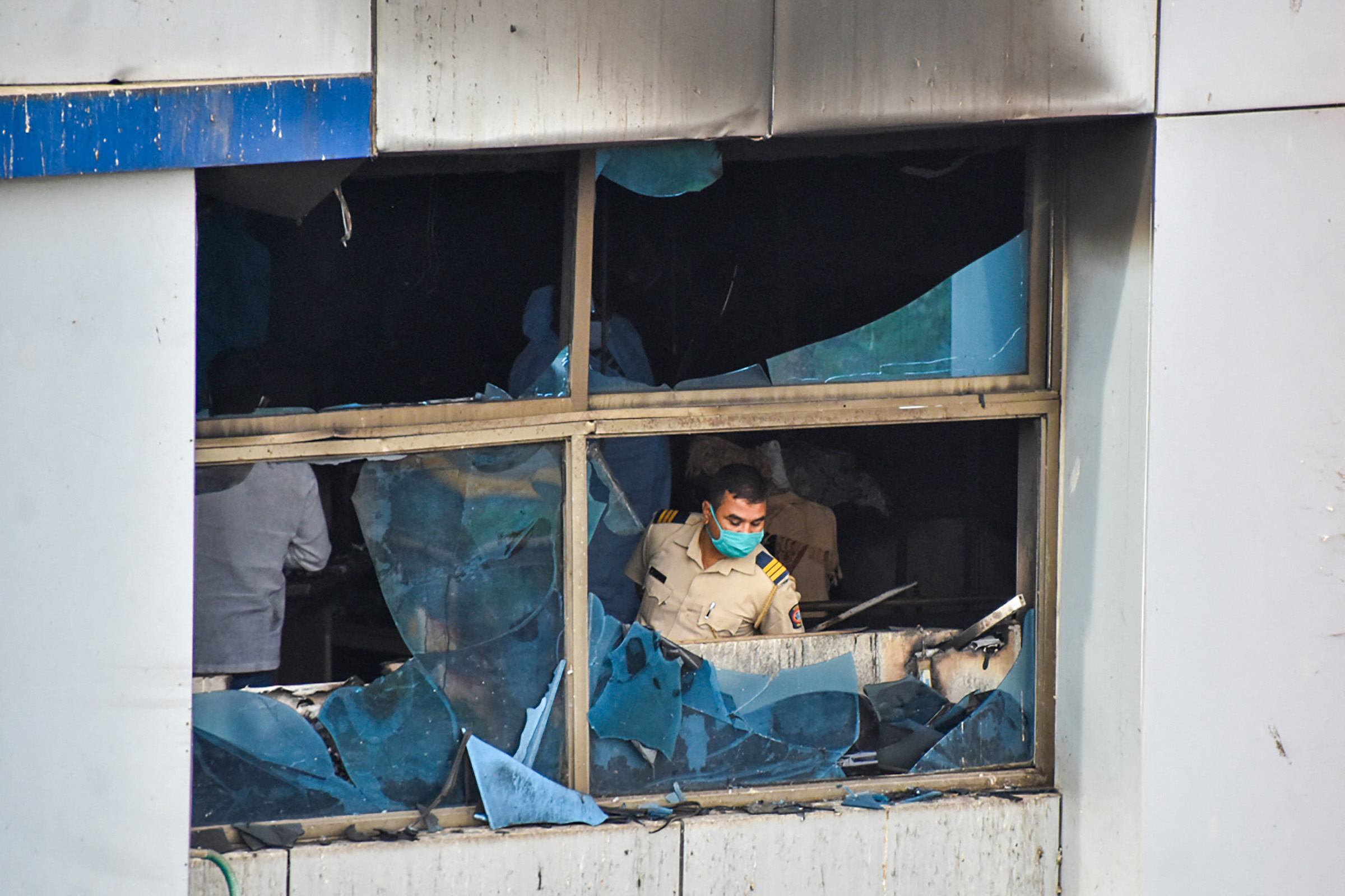 A policeman inspects a burnt-out room at the Vijay Vallabh Hospital in Virar, on the outskirts of Mumbai, after a fire broke out in the hospital's ICU, on Friday, April 23.