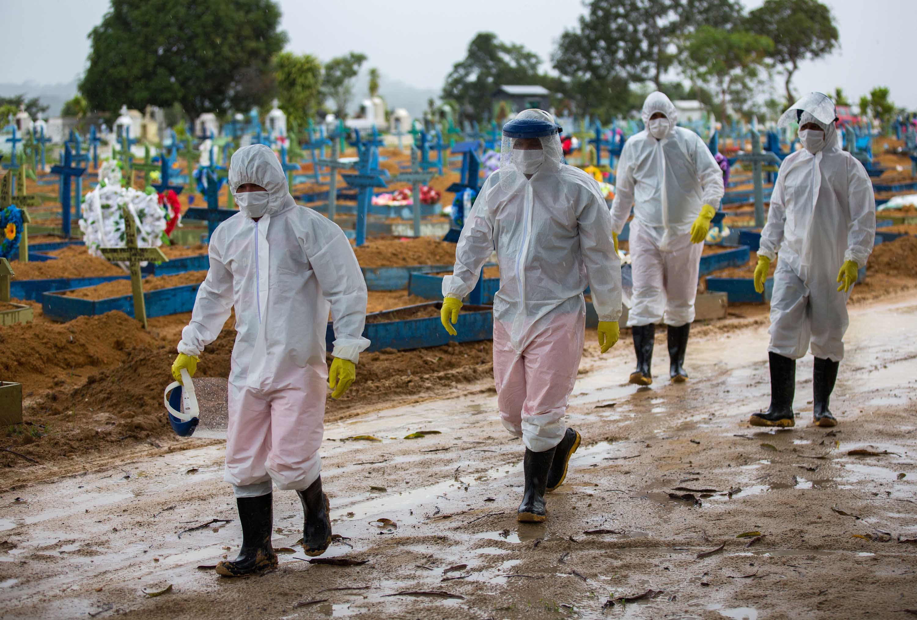 Workers wearing protective suits walk past the graves of COVID-19 victims at the Nossa Senhora Aparecida cemetery, in Manaus, Brazil, on February 25.