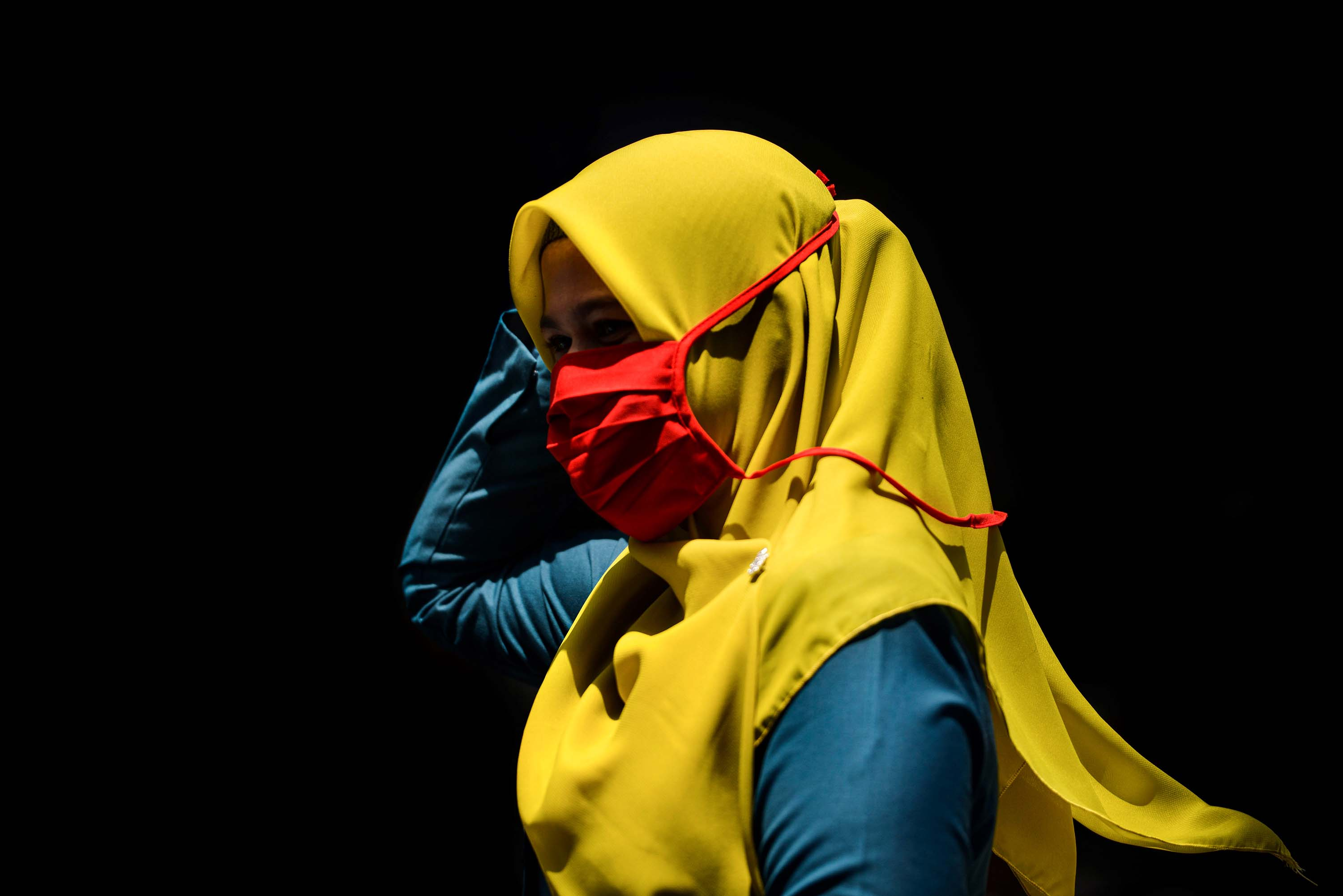 A woman wearing a face mask walks through a market in Banda Aceh, Indonesia on March 24.