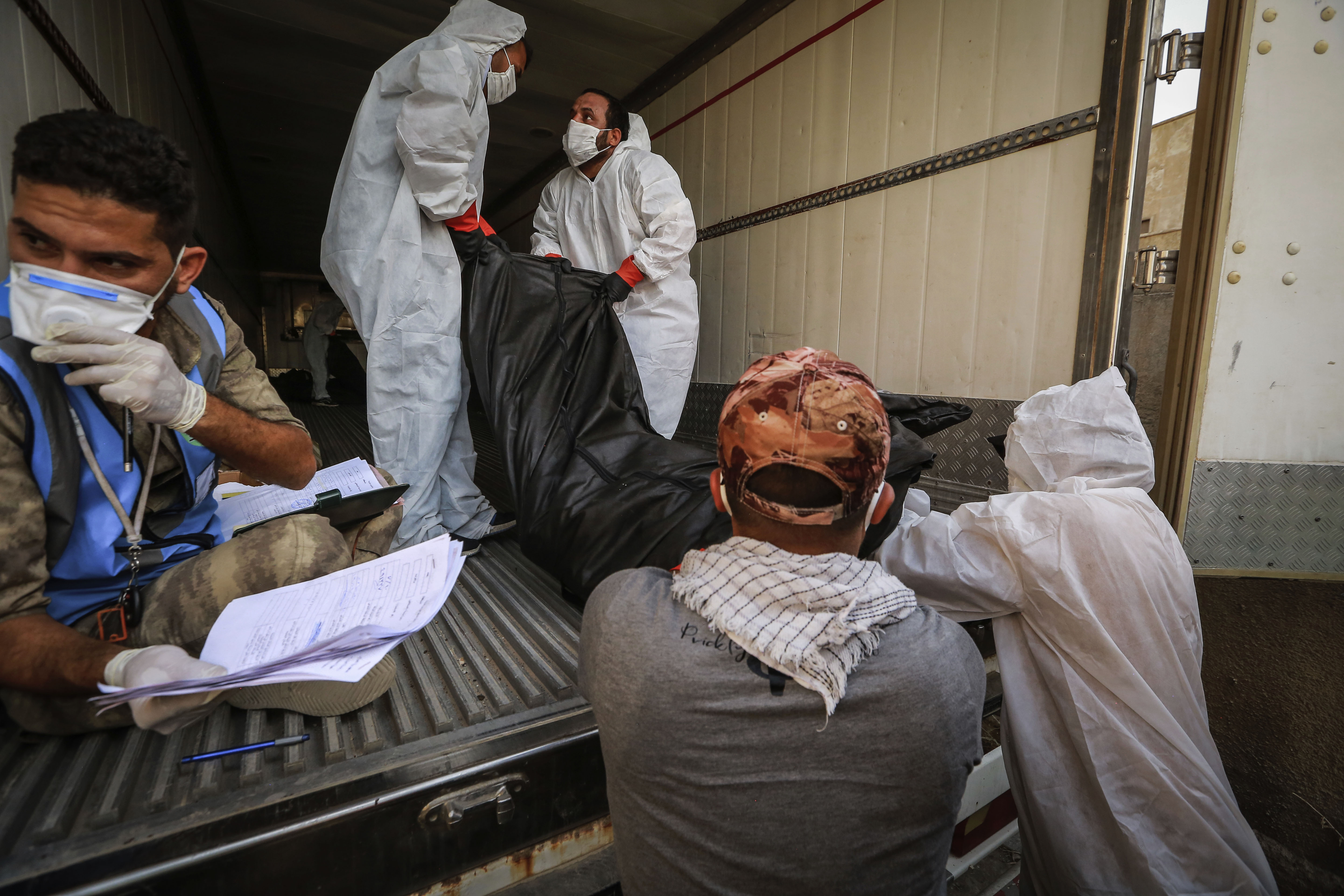 Workers in Baghdad, Iraq, put the body of a person said to have died from Covid-19 into a refrigerator truck to be transferred on July 11.