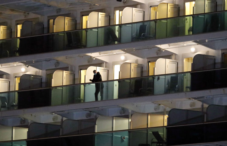 A passenger stands on a cabin balcony of the Diamond Princess cruise ship docked at the Daikoku Pier Cruise Terminal in Yokohama, Japan, on Tuesday, February 18.