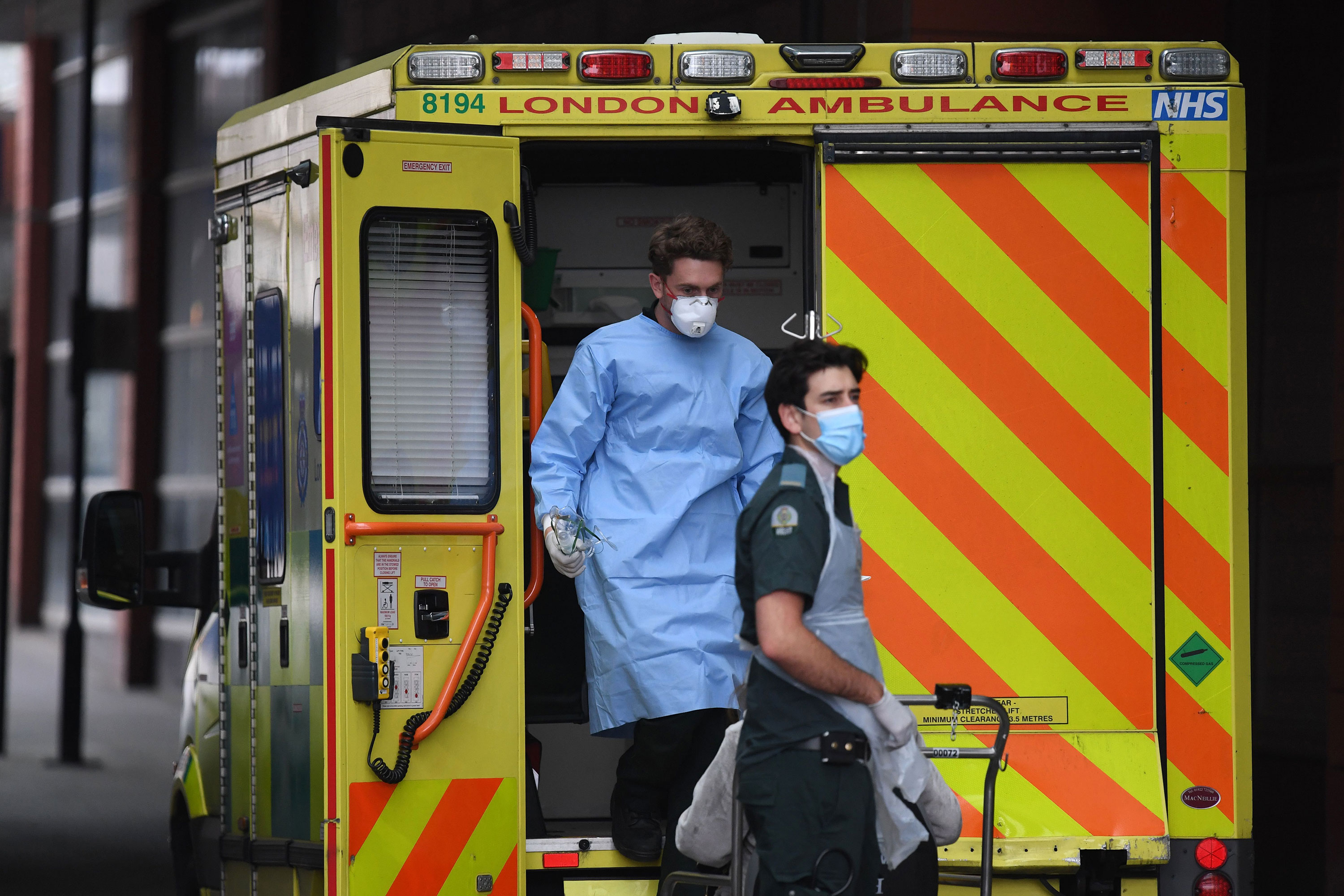 Paramedics wearing personal protective equipment help a patient from an ambulance into the Royal London Hospital on April 18.