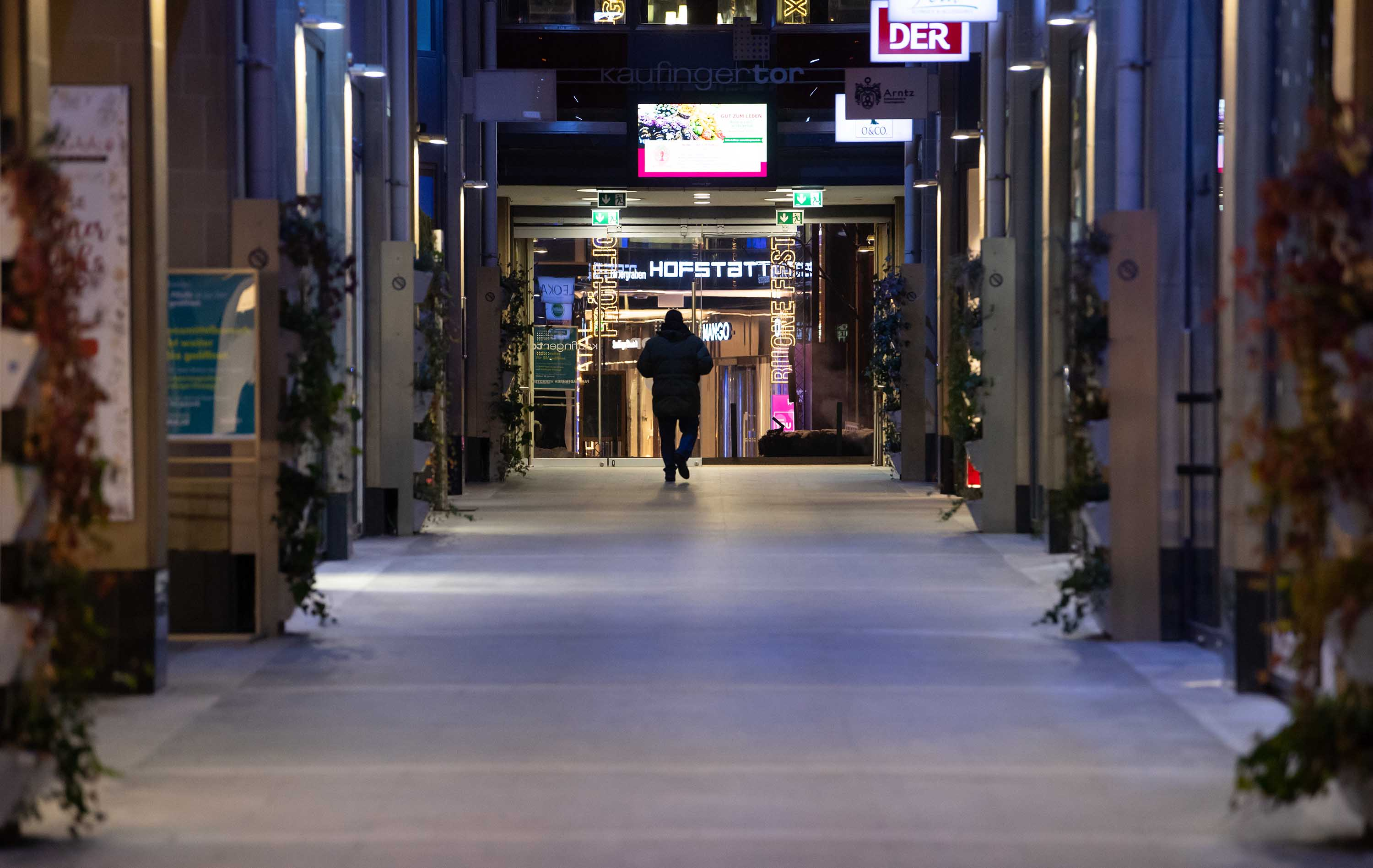 A person walks through a deserted shopping arcade in Munich, Germany, on Monday, January 11.