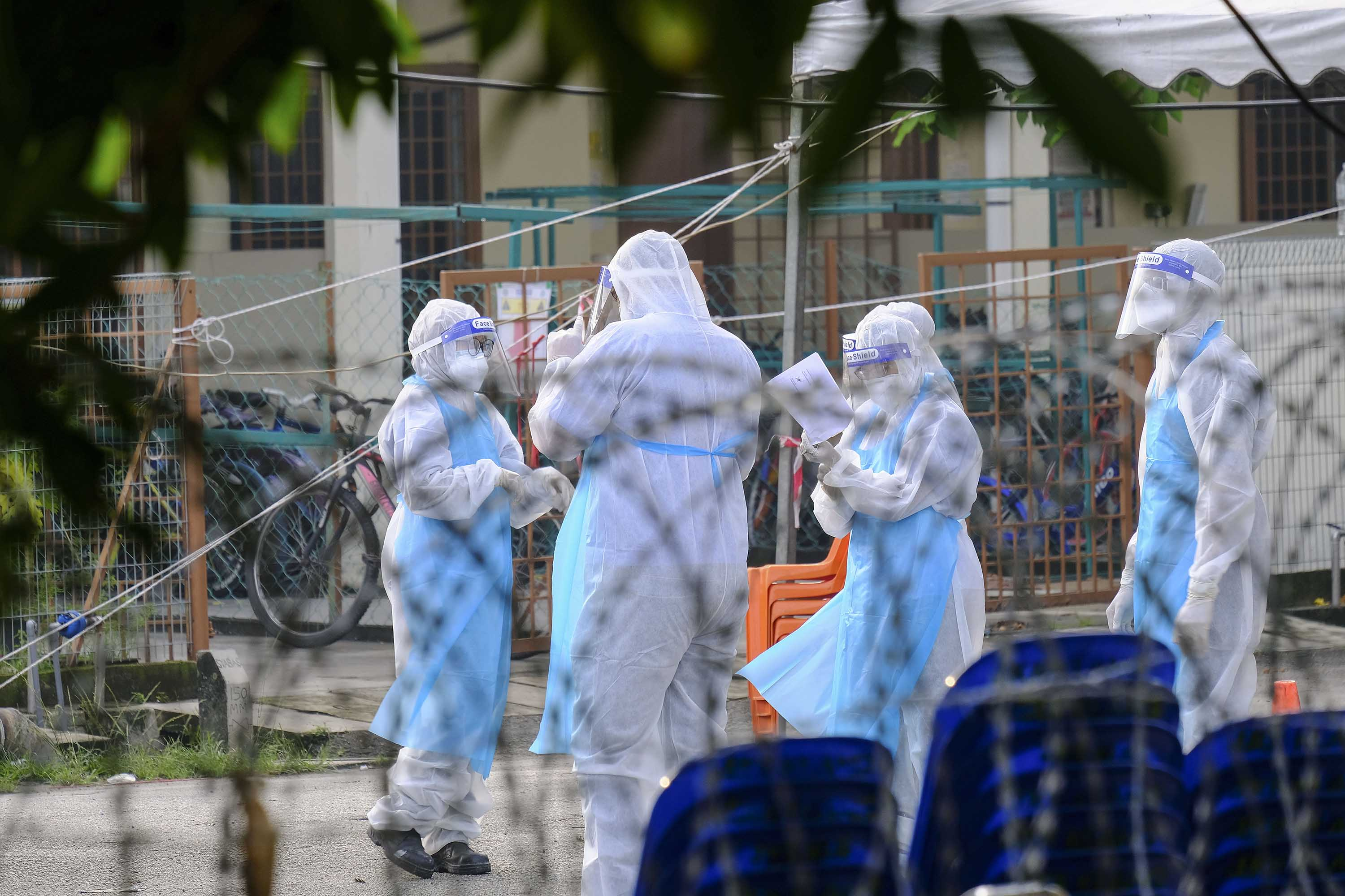 People wearing protective suits are seen behind barbed wire at the Top Glove hostel compound in Klang, Malaysia, on November 23.