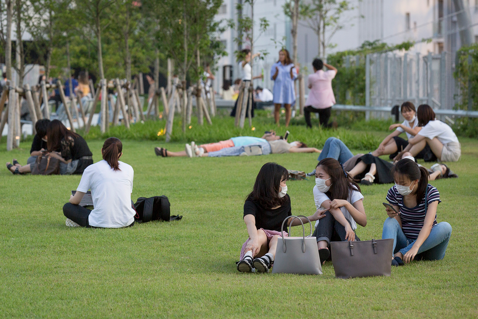 People wearing face masks relax on the grass at Miyashita park on August 4, 2020 in Tokyo.