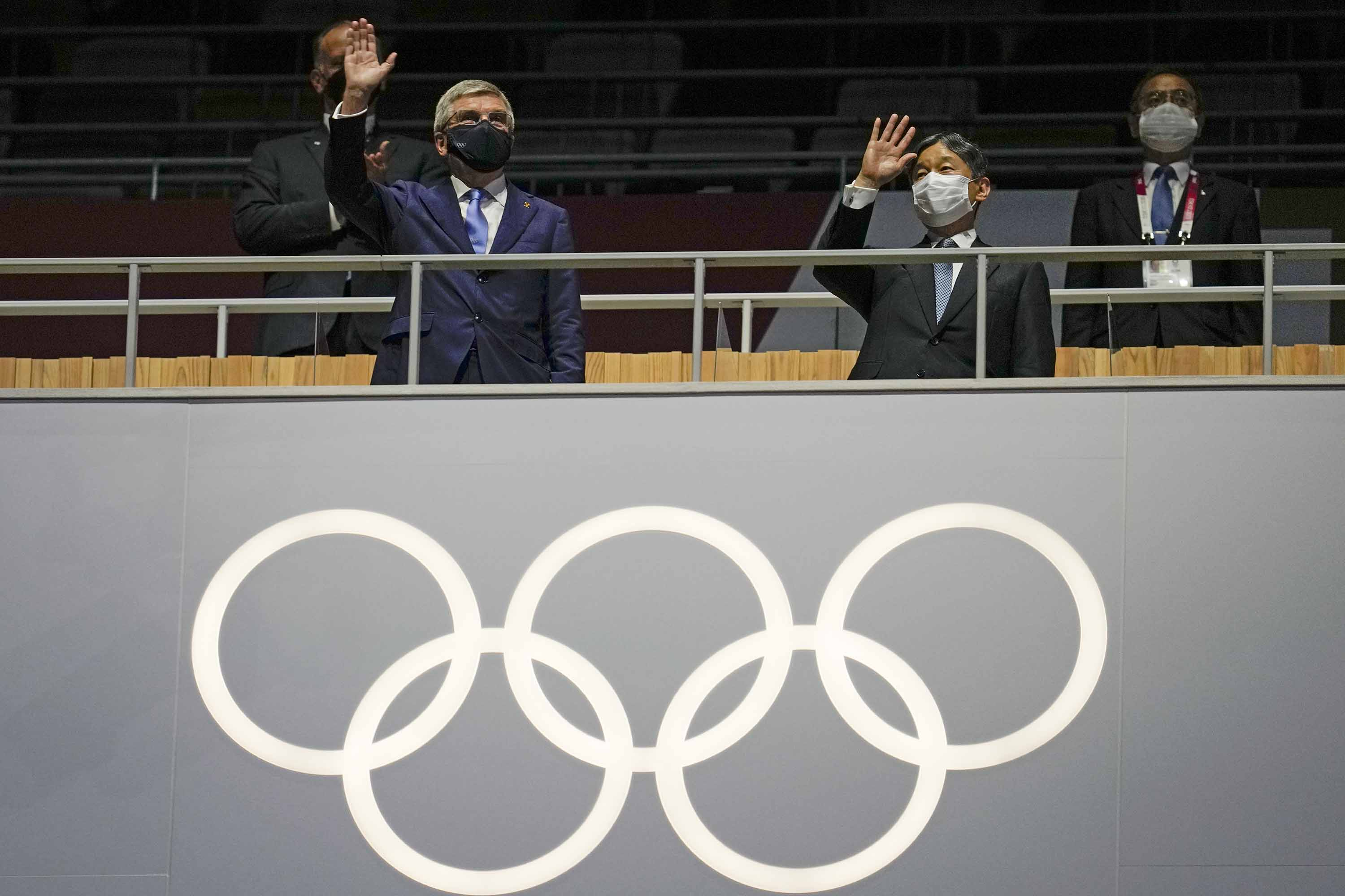 Japan's Emperor Naruhito, right, and President of the IOC Thomas Bach wave during the Opening Ceremony.