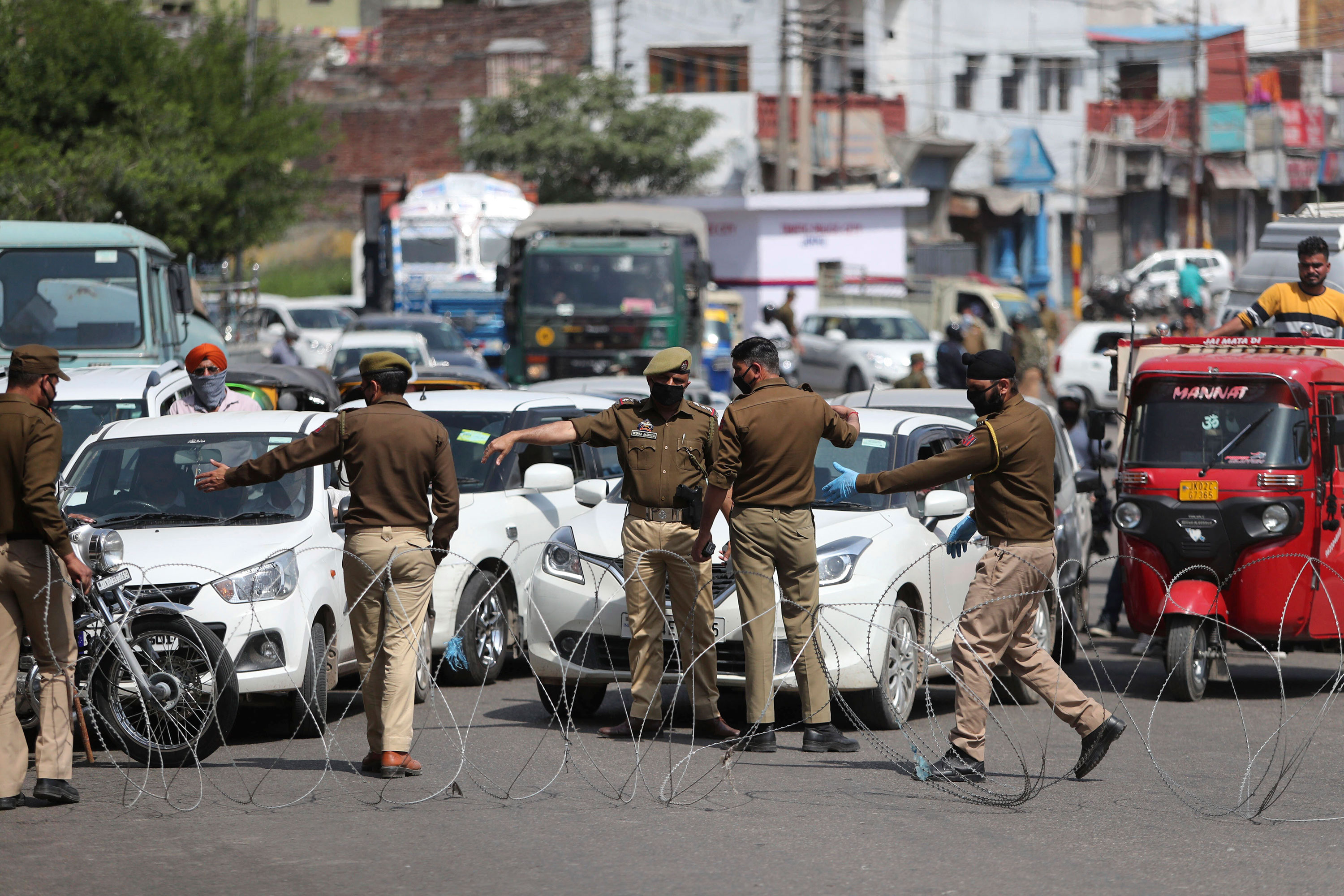 Policemen erect barbed wire to stop commuters as they enforce a lockdown in Jammu, India on March 23.
