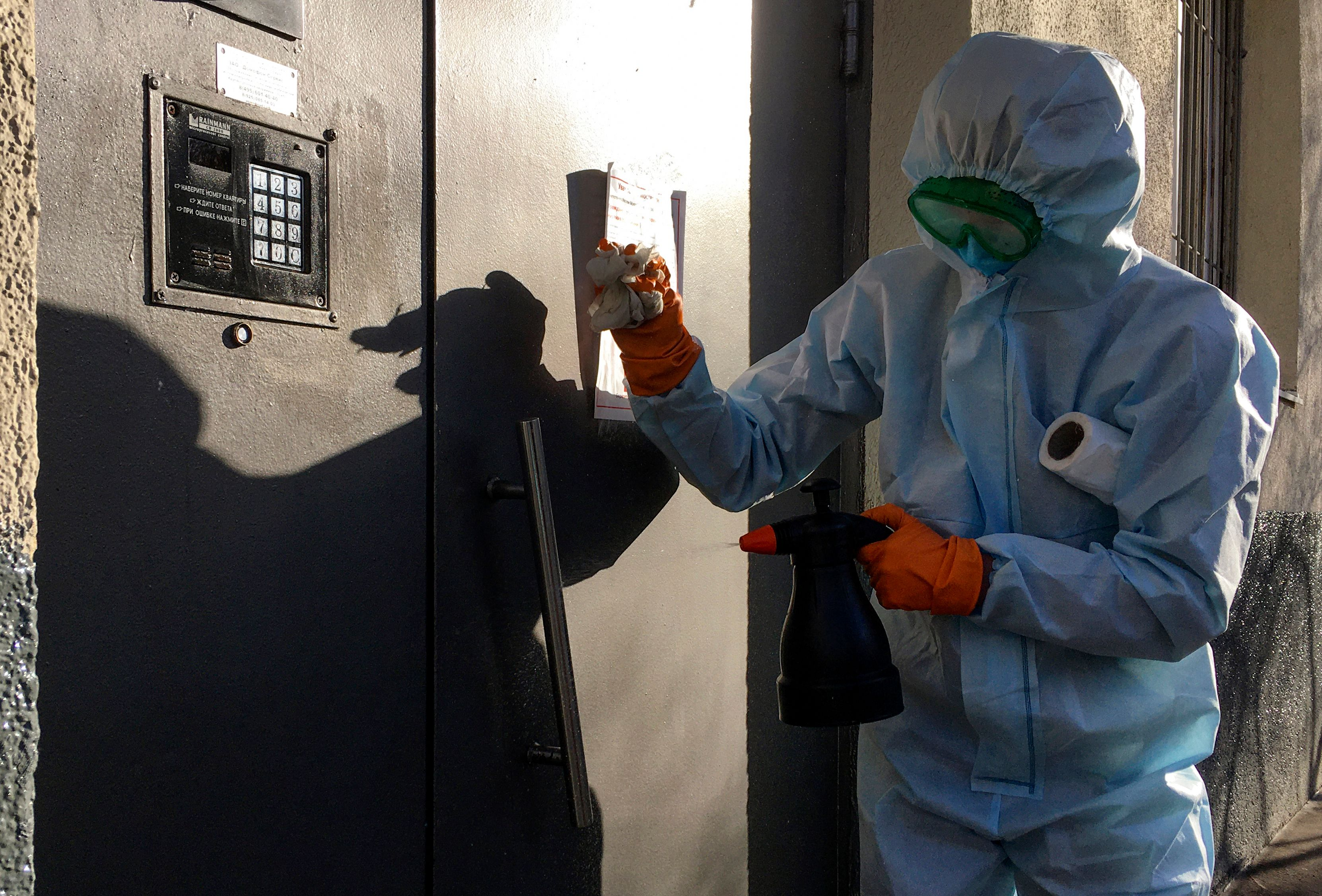 A communal worker sprays disinfectant on the door of a residential building in Moscow on April 11.