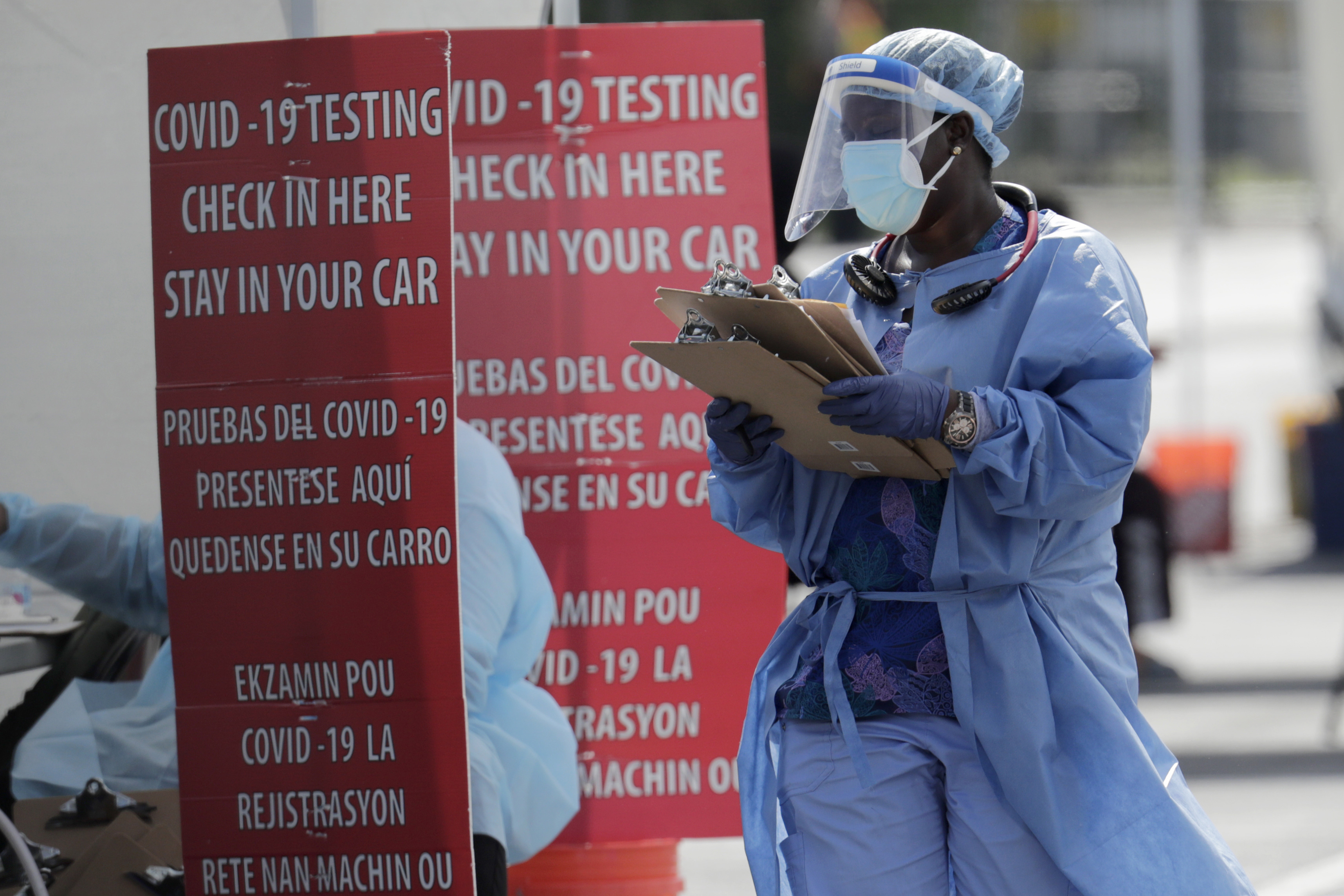 A health care worker carries a stack of clipboards at a Covid-19 testing site on July 6, in Homestead, Florida.
