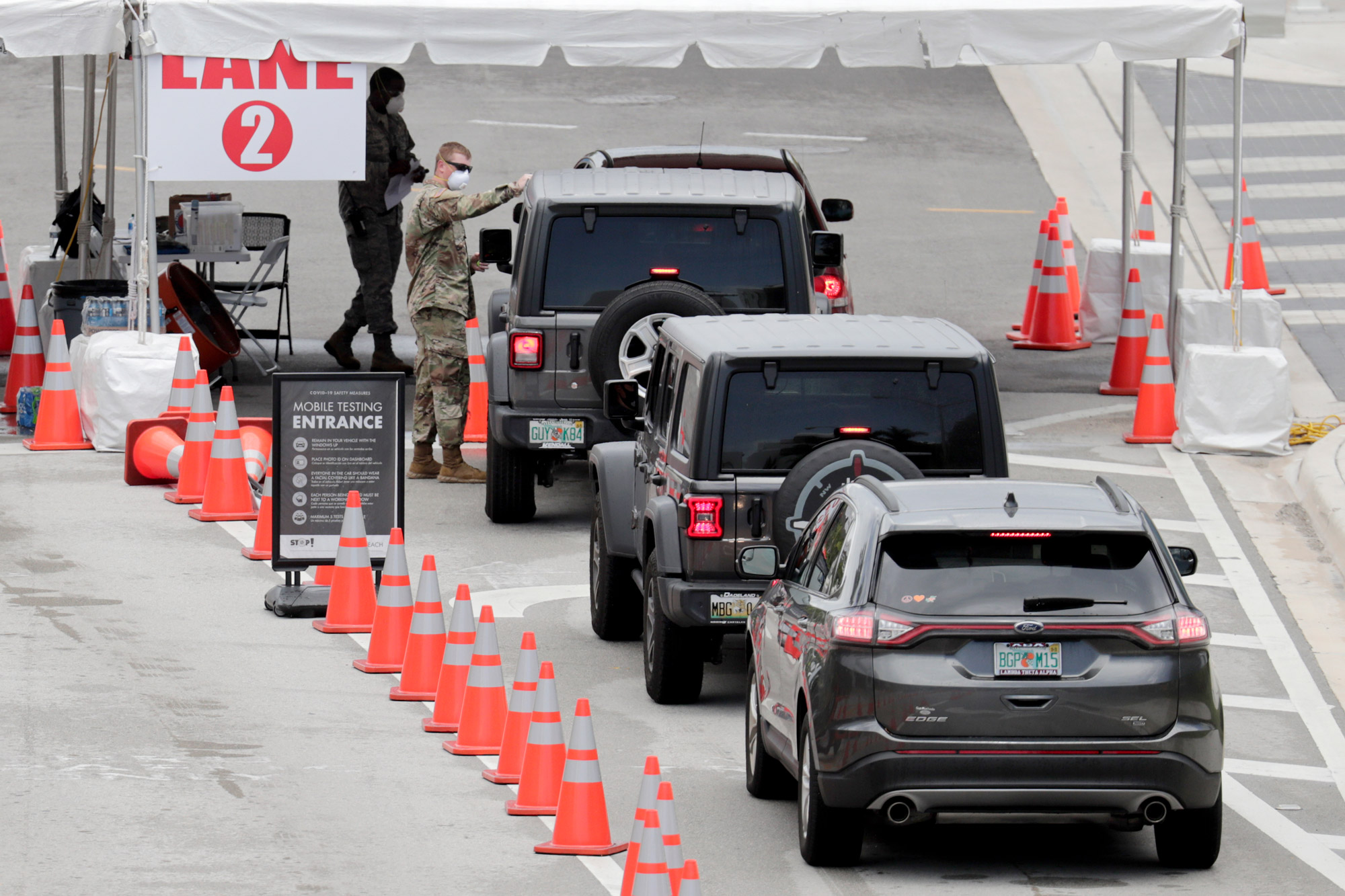 A member of the Florida National Guard directs vehicles at a COVID-19 testing site at the Miami Beach Convention Center on July 12 in Miami Beach, Florida.