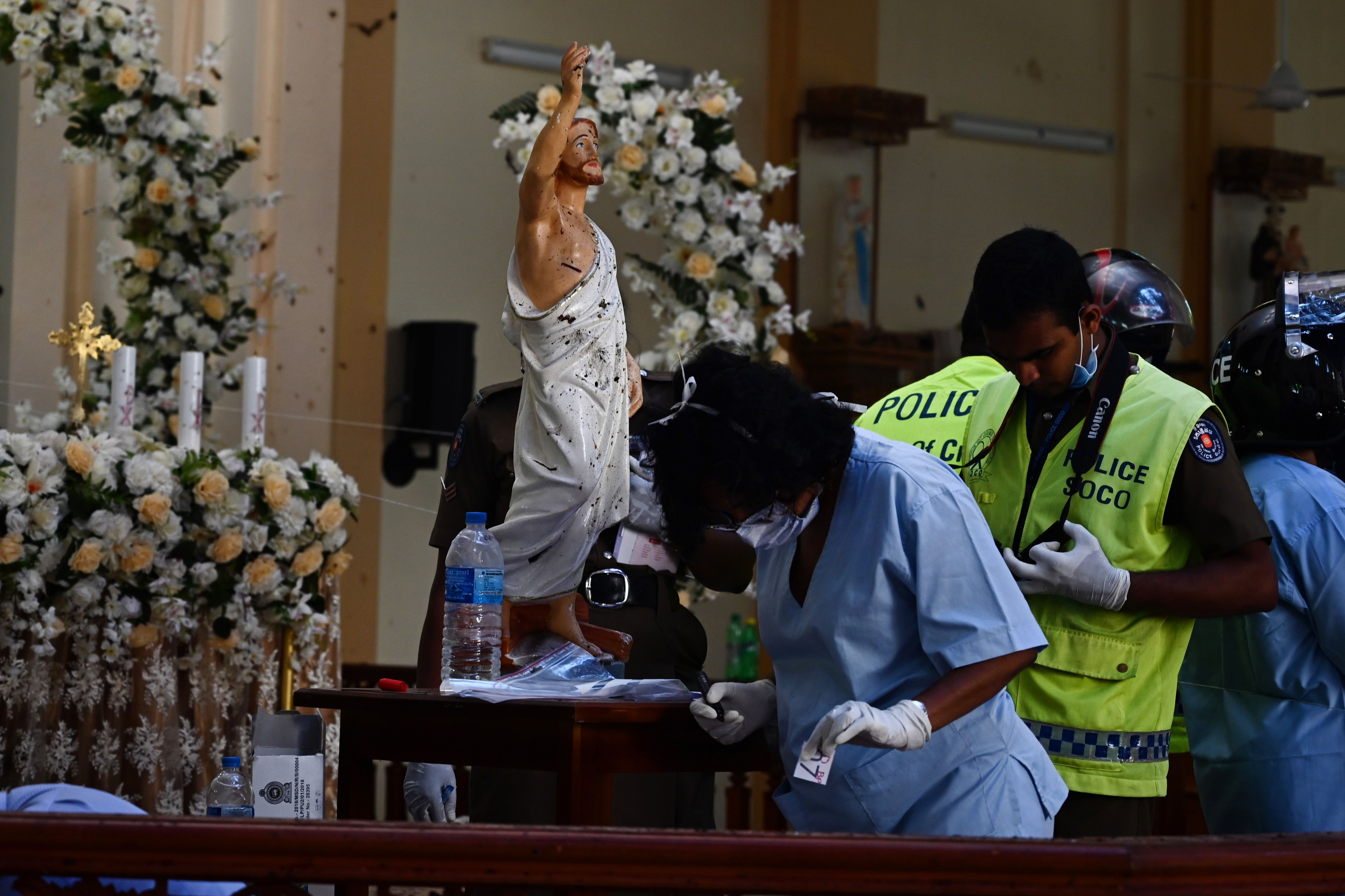 Security personnel inspect the interior of St Sebastian's Church in Negombo on Monday, a day after the church was hit in series of bomb blasts.