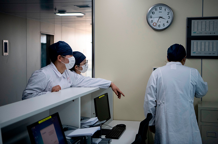 Nurses talk inside the finished but still unused building A2 of the Shanghai Public Clinical Center, where coronavirus patients will be quarantined, in Shanghai on February 17.