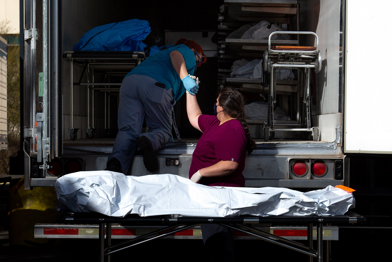 Employees prepare to move a body into a refrigerated semi-truck at the Pima County Office of the Medical Examiner on January 14, in Tucson, Arizona.
