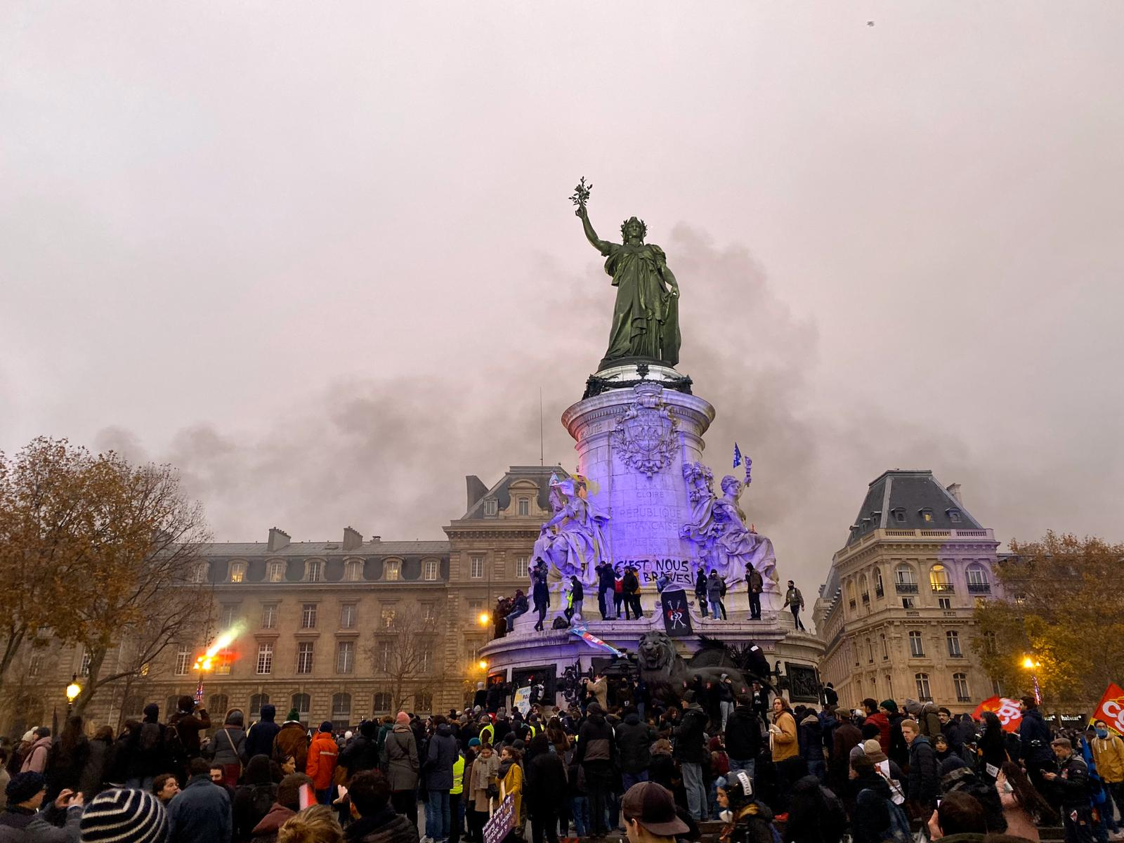 Protestors gather around a statue at Place de la République which represents Marianne, a fictional woman who represents the French Republic since the revolution.