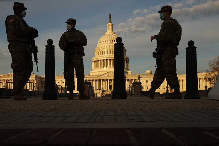 Members of the New York National Guard stand guard along the fence that surrounds the U.S. Capitol on January 14, 2021 in Washington, DC.