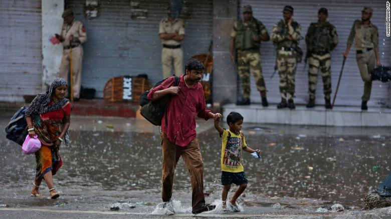 Indian security take shelter in front of closed shops as stranded tourists walk in the rain during a security lockdown in Jammu on Monday.