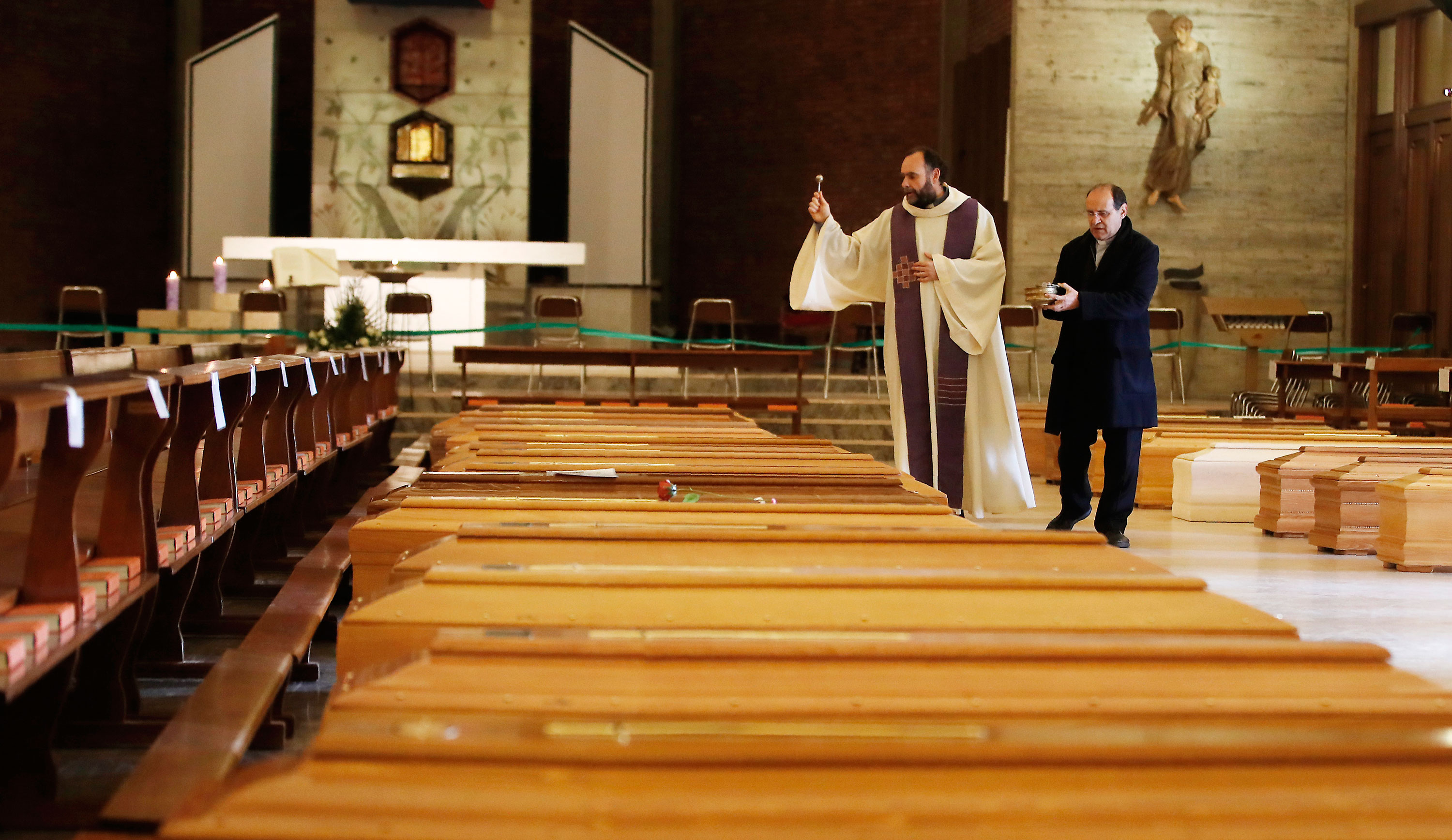 Don Marcello Crotti, on the left, blesses the coffins with Don Mario Carminati at San Giuseppe Church in Seriate, Italy, on March 28.