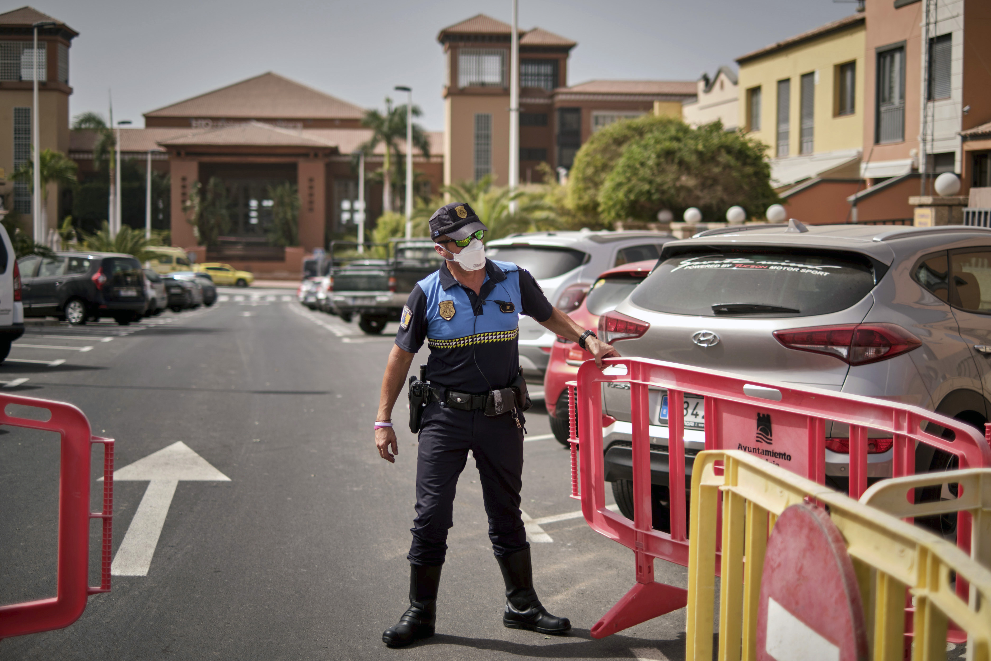 A Spanish police officer sets up a barrier blocking the access to the H10 Costa Adeje Palace hotel in Tenerife, Canary Island, Spain, on Tuesday, February 25.