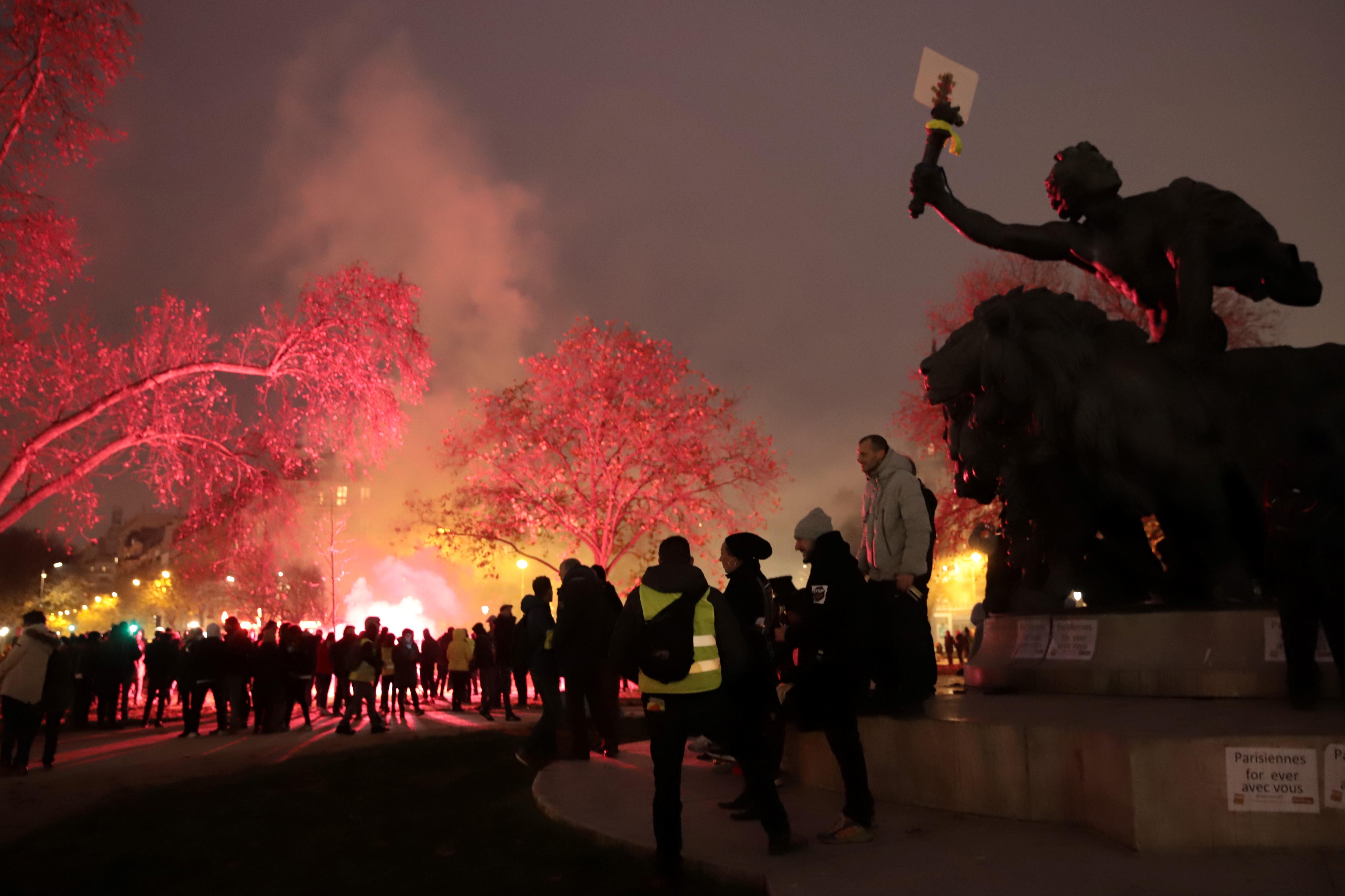 "Protesters gather near the ""Triomphe de la Republique"" statue among flares."