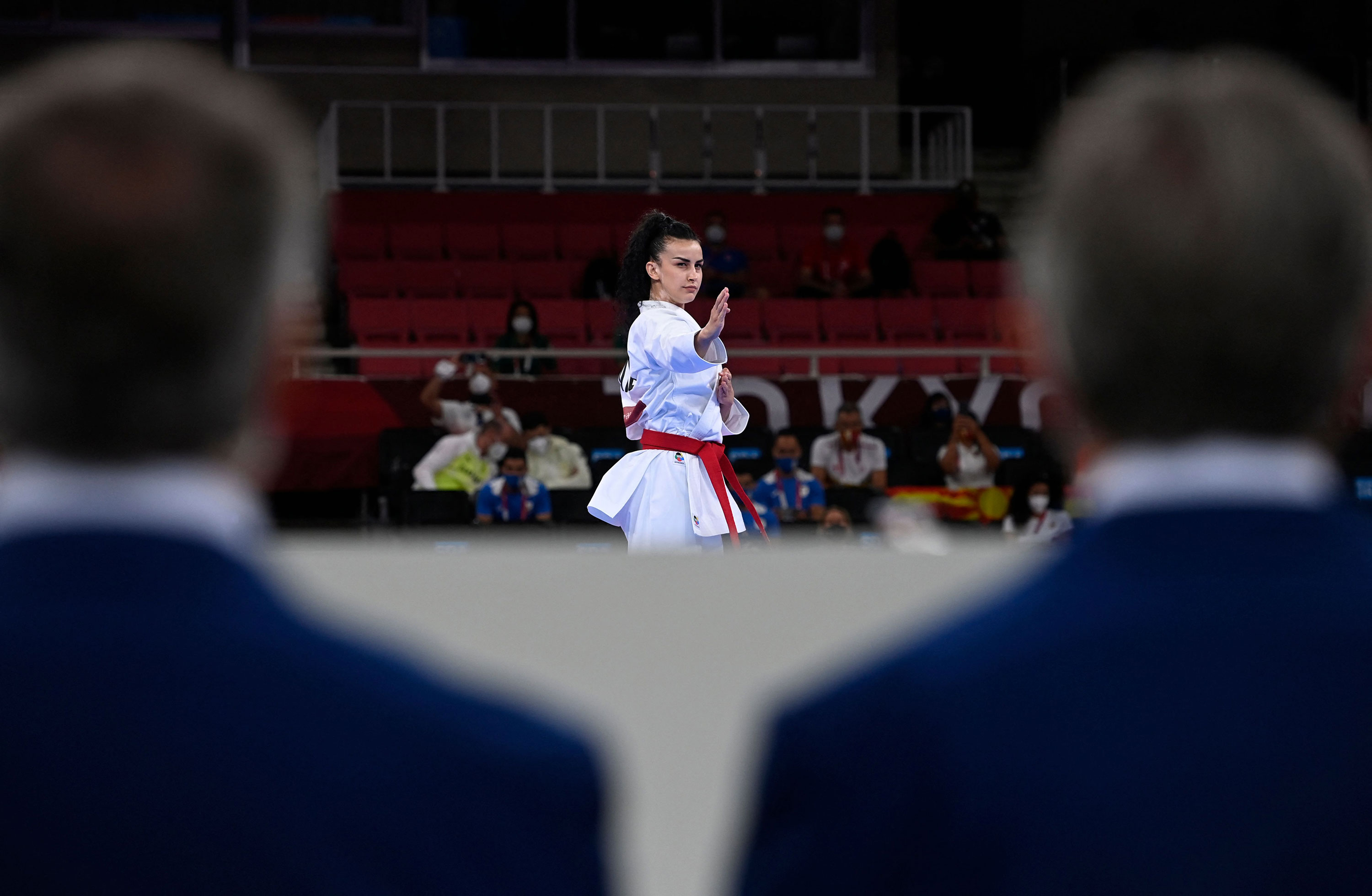 Judges watch North Macedonia's Puliksenija Jovanoska competes in the kata event of karate competition on August 5.