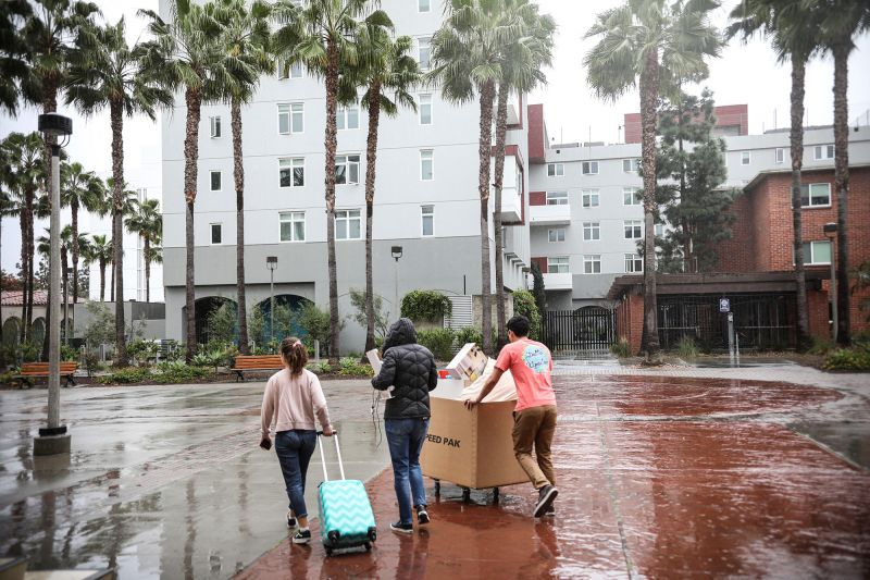 In this March 18 file photo, students and their parents move their belongings from their dormitories at San Diego State University.
