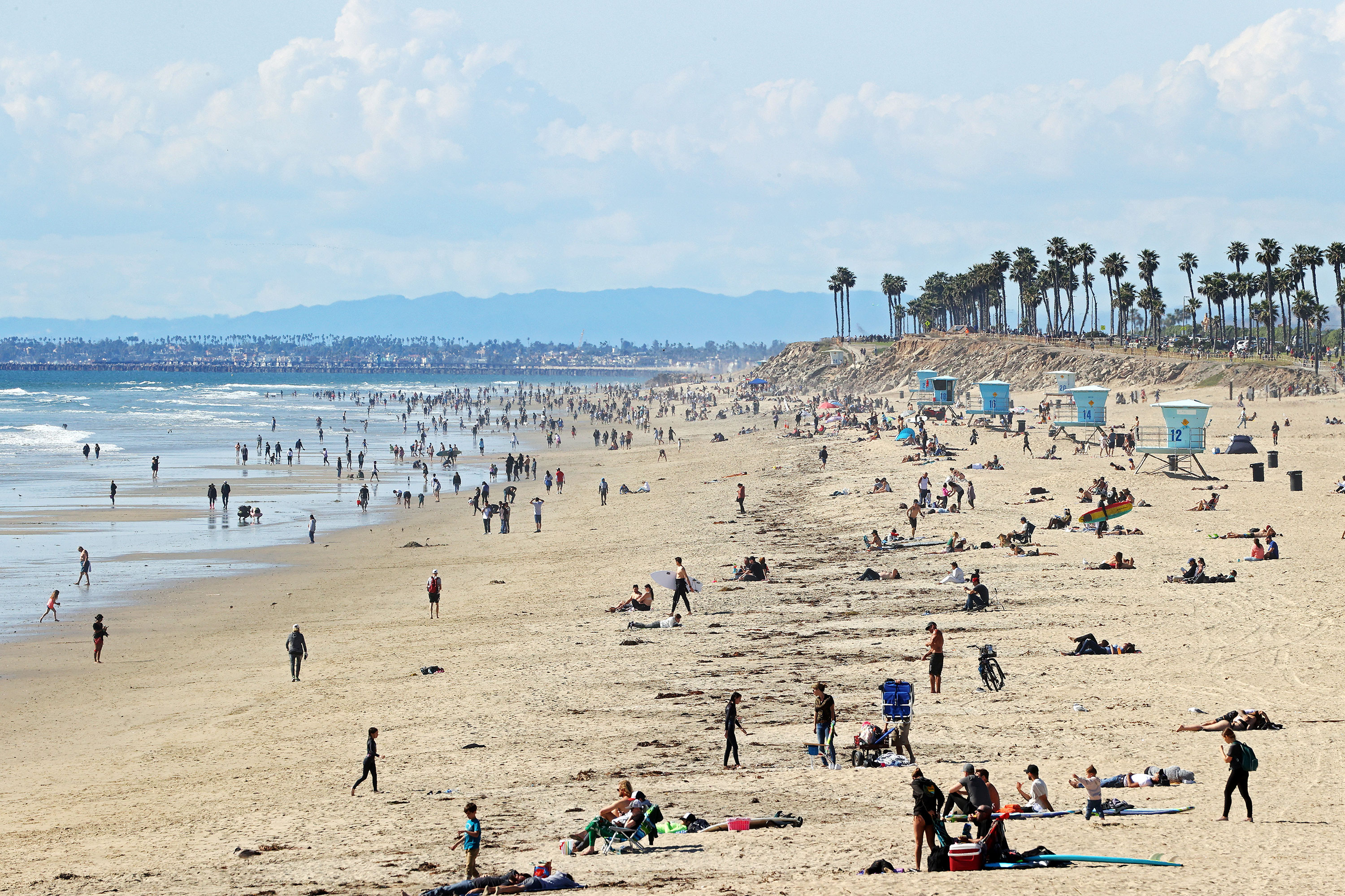 People are seen on the beach in Huntington Beach, California on March 21.