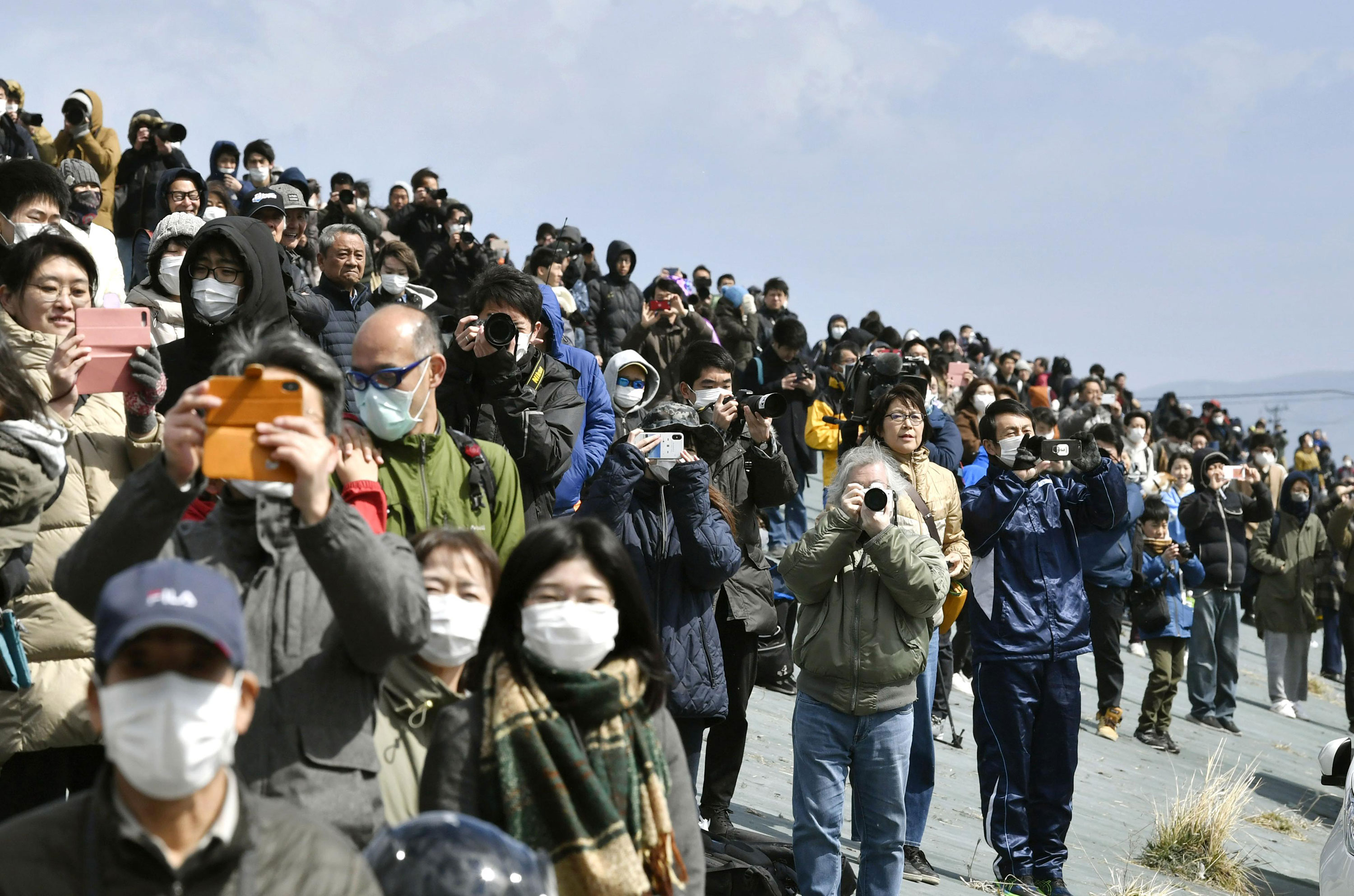 People watch the Japanese Air Self-Defense Force's Blue Impulse aerobatics team in Higashimatsushima, Miyagi, on March 20, where the Olympic flame arrived from Greece.
