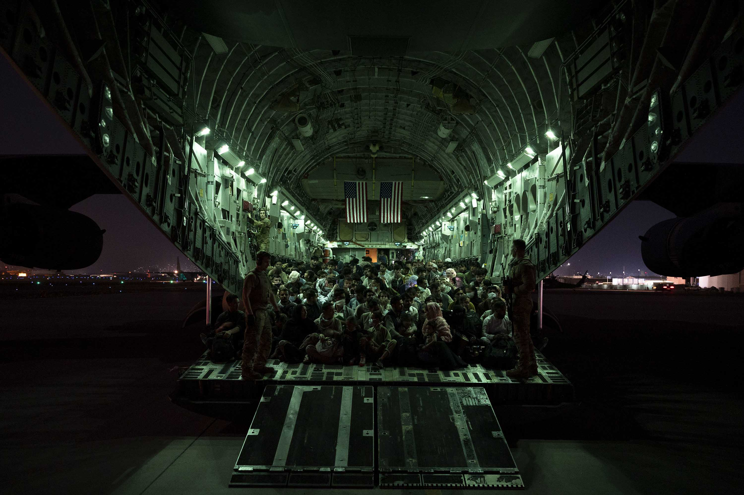 In this handout photo provided by the U.S. Air Force, an air crew assists evacuees aboard a C-17 Globemaster III aircraft during evacuations at Hamid Karzai International Airport on August 21.