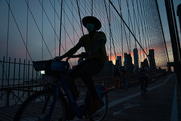 A cyclist wearing a facemask rides over the Brooklyn Bridge during sunset on August 21, 2020 in New York.
