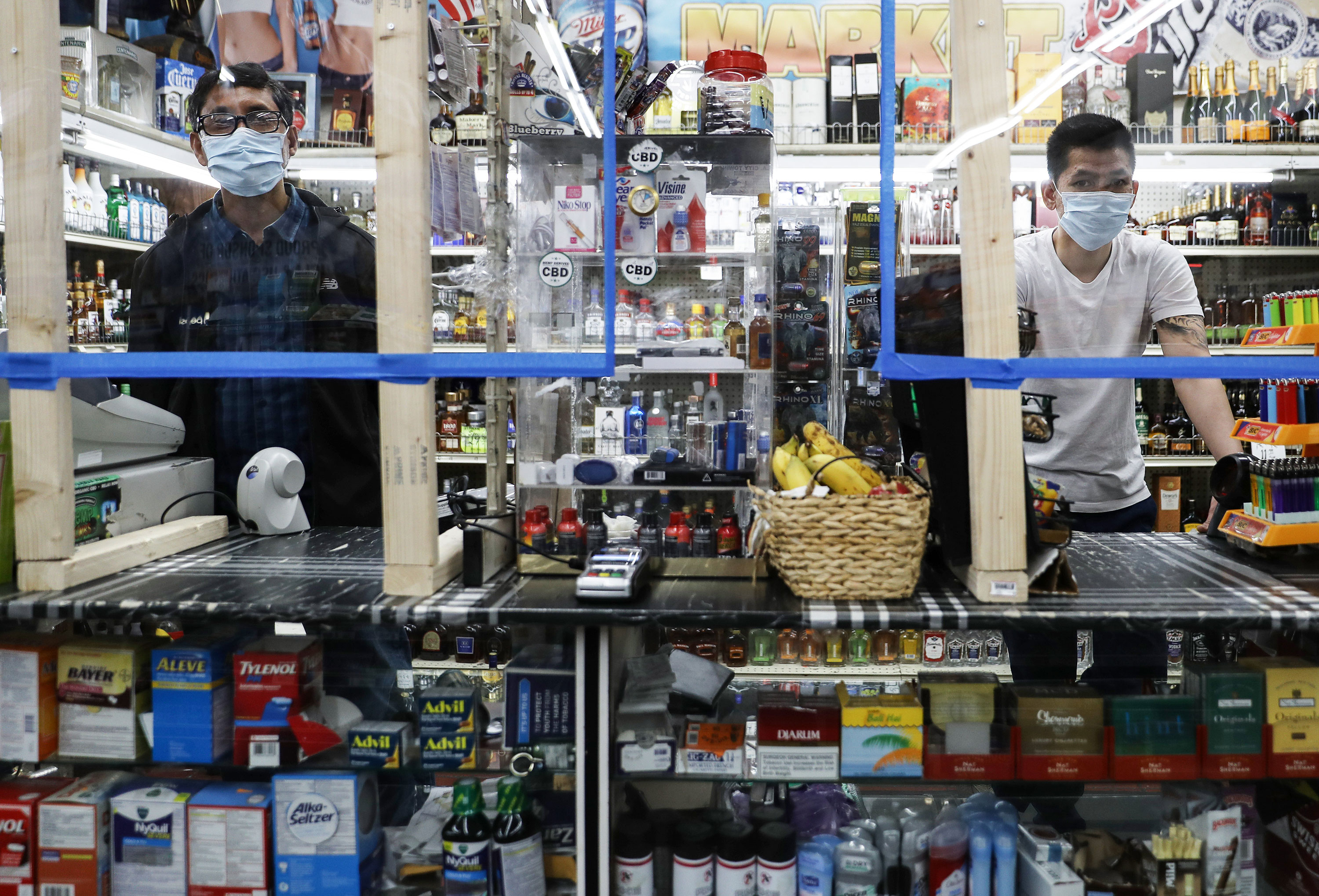 Cashiers wear face masks at a convenience store in Los Angeles, California on April 4.