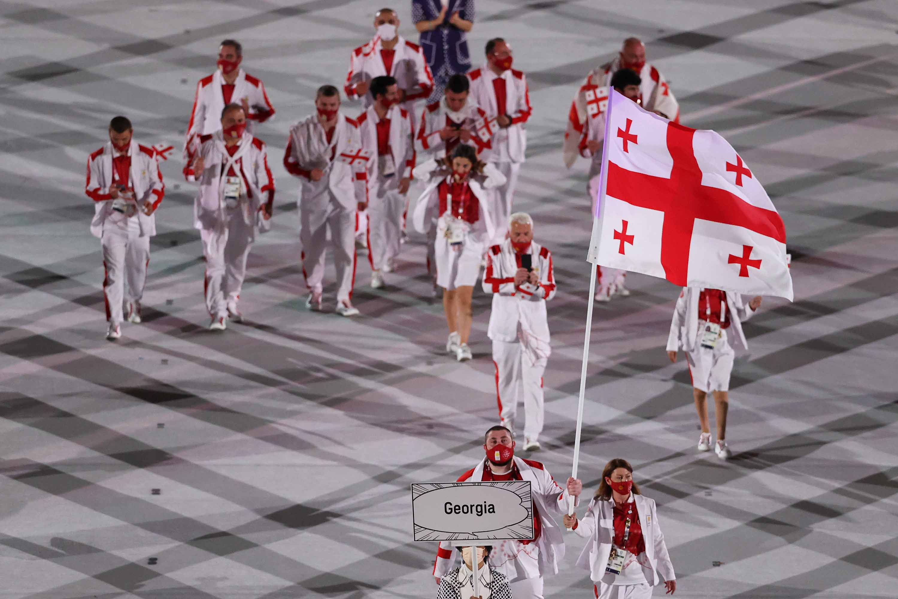 Flag bearers Nino Salukvadze, right, and Lasha Talakhadze of Team Georgia lead their team out during the Opening Ceremony of the Tokyo 2020 Olympic Games on July 23.