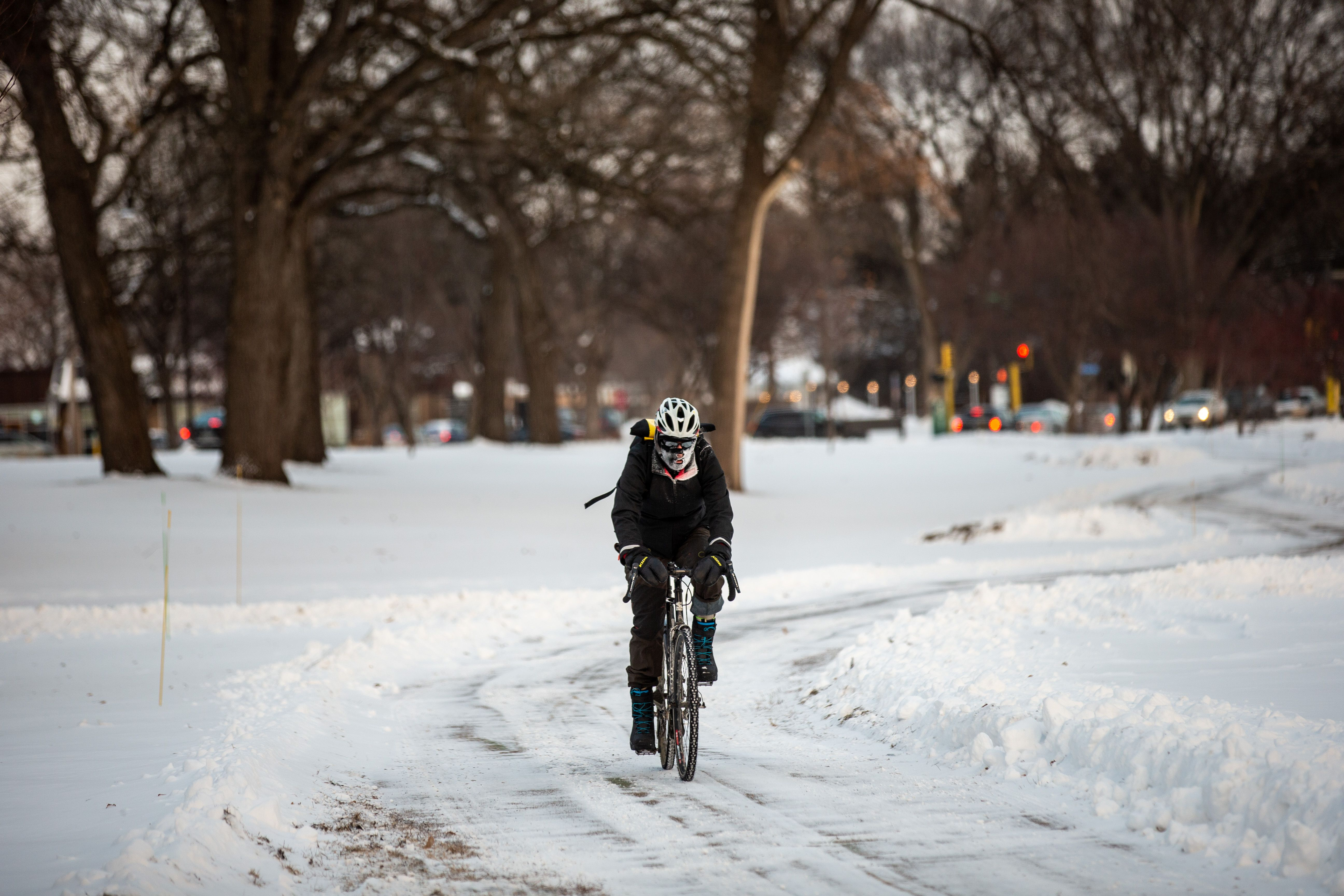 A bicyclist passes through heavy frost in Nokomis parkway, south west Minneapolis, as temperatures in the area dipped below freezing on Tuesday.