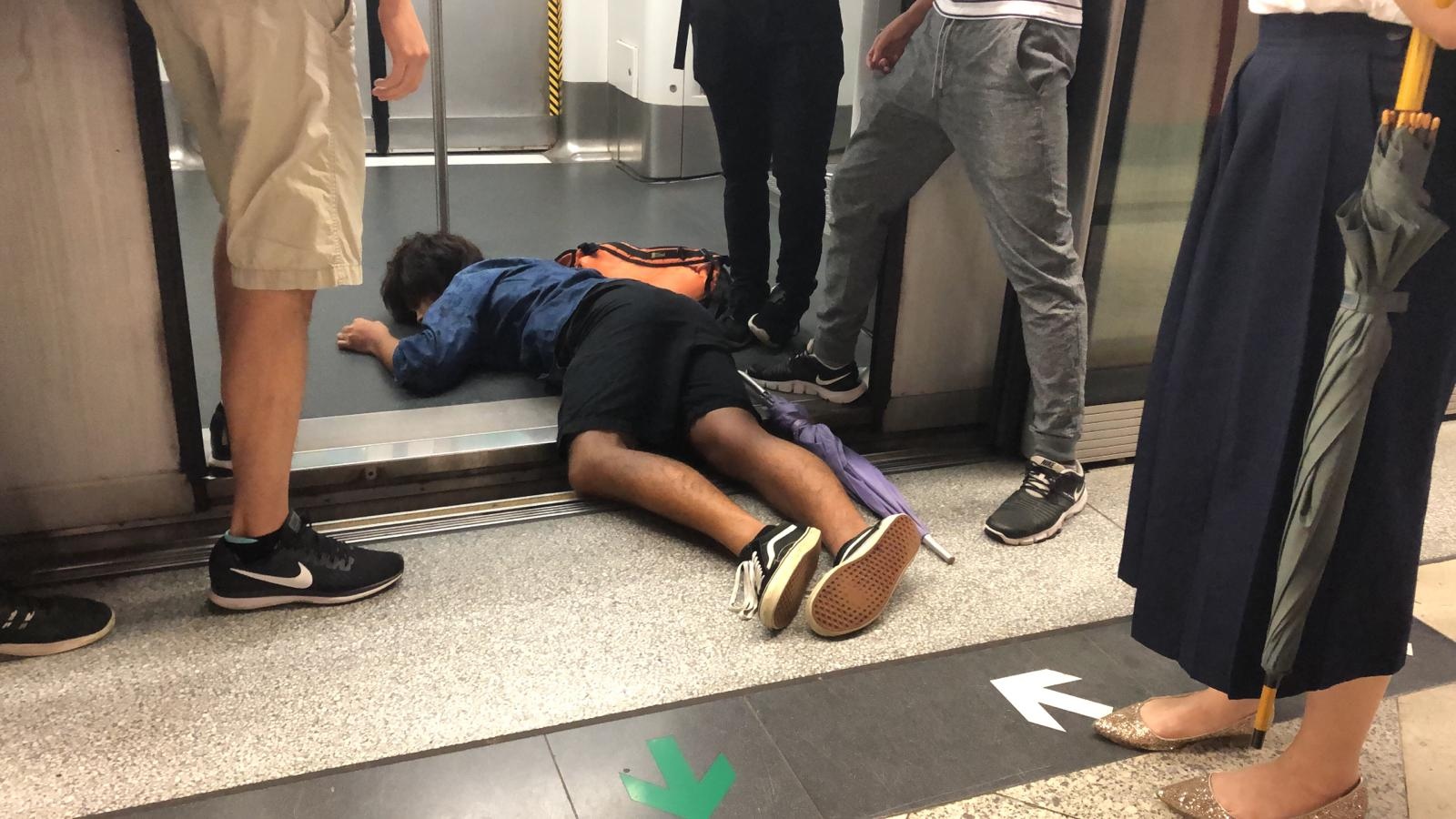 A protester lies on the floor, preventing the train from leaving in Hong Kong.