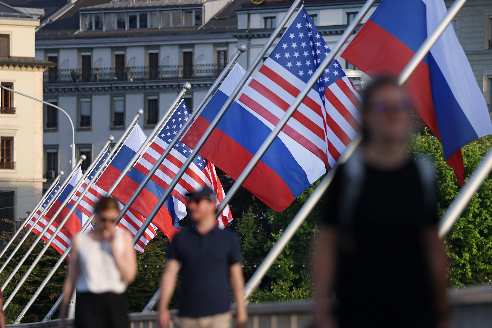 People walk under Russian and American flags on a bridge in the city center prior to a meeting between US President Joe Biden and Russian President Vladimir Putin on June 15, in Geneva, Switzerland.